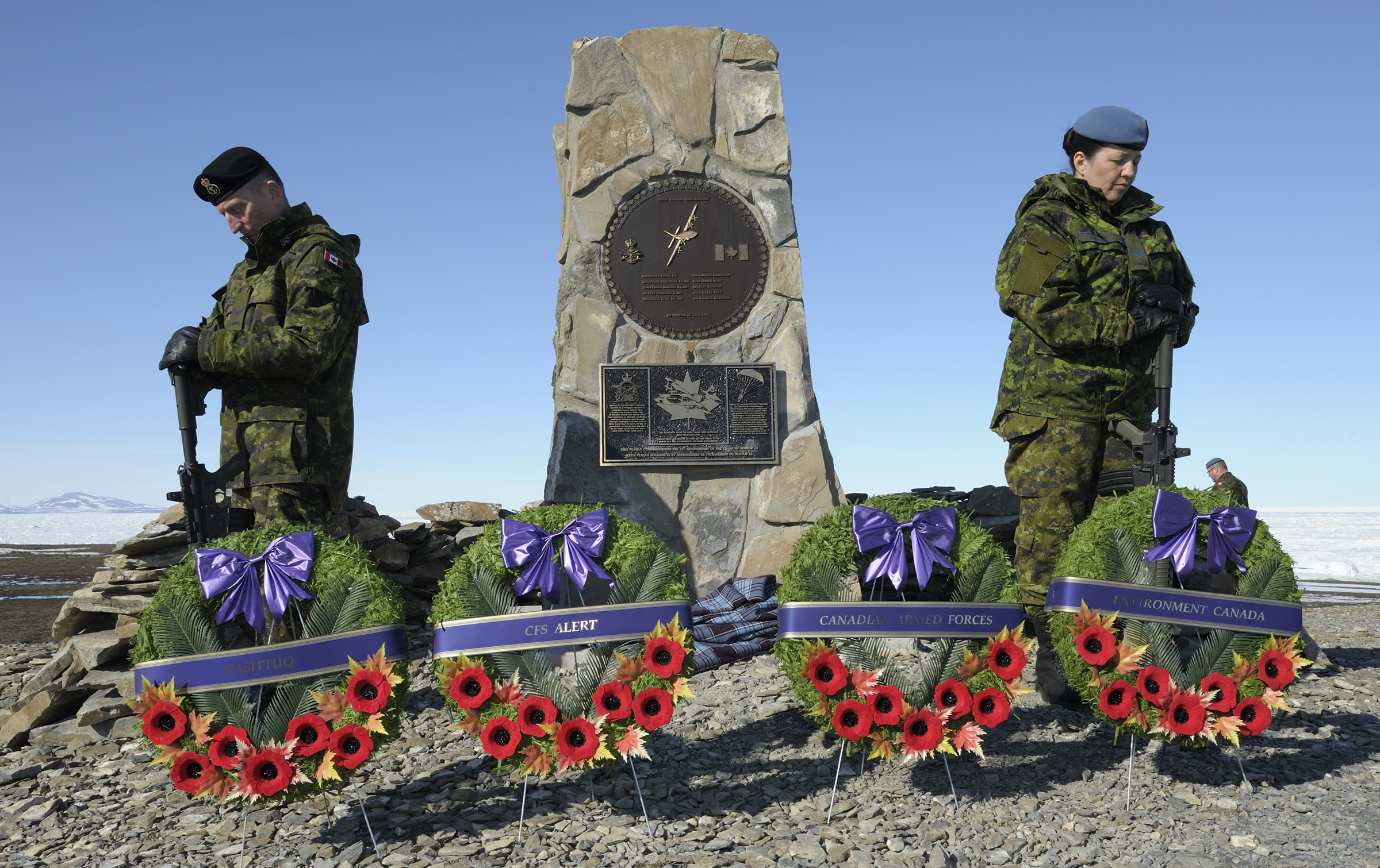 Sentries stand at a stone cairn at CFS Alert that commemorates the crash of Boxtop 22. A new plaque, identical to the one on the new cairn that now stands at 8 Wing Trenton, was added to the Alert cairn and unveiled in June 2016. PHOTO: Sergeant Paz Quillé, FA02-2016-0016-27