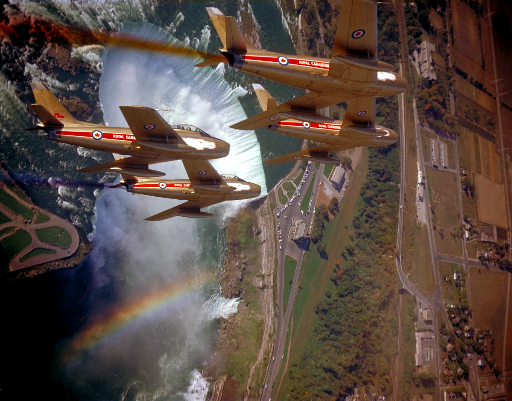 Four small jets, painted in colours of gold and red, fly at a steep angle over Horseshoe Falls at Niagara Falls, Ontario.