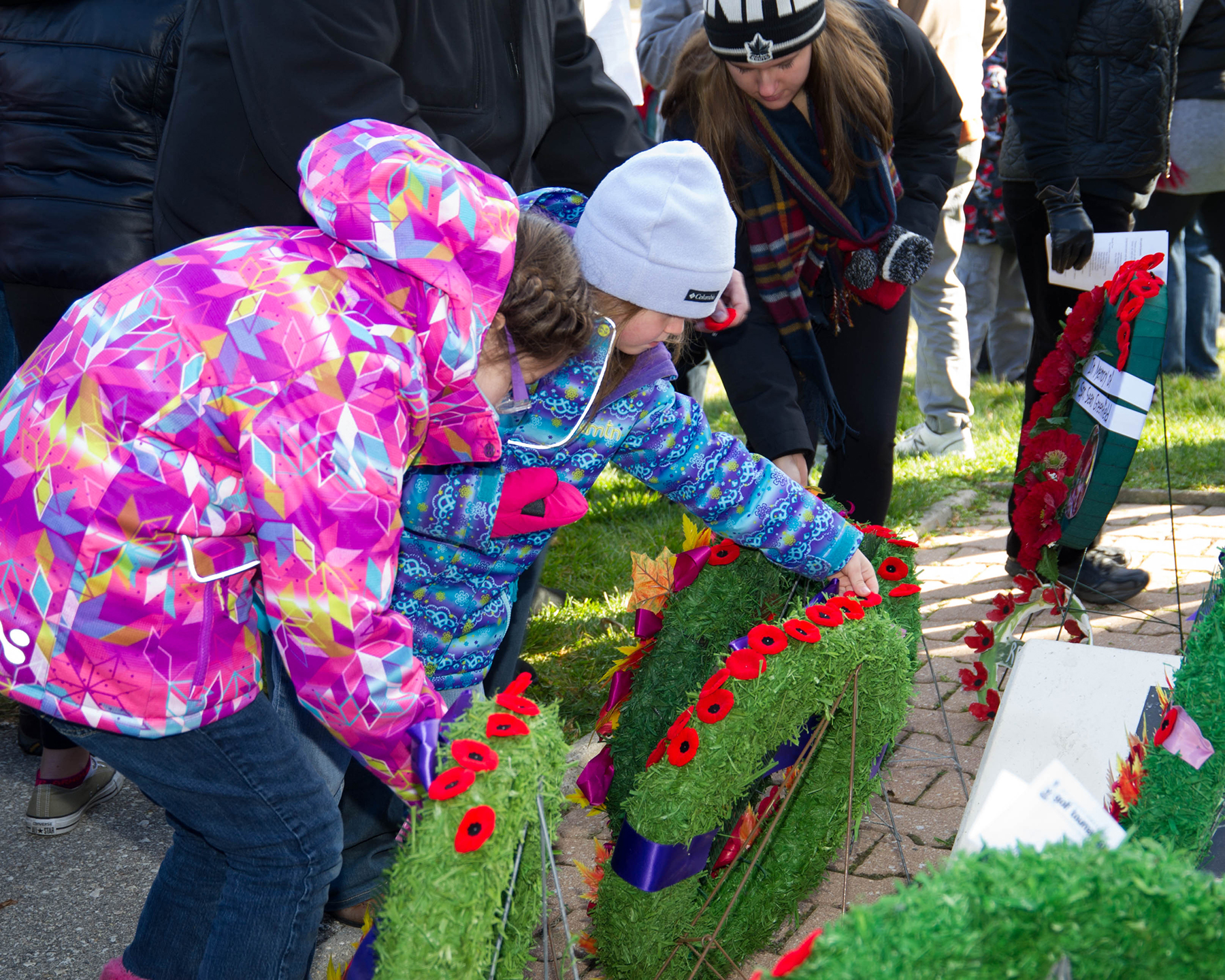 Children leave their poppies on wreaths in Bruce Park, Winnipeg, Manitoba, after the Remembrance Day ceremony on November 11, 2016. PHOTO: Corporal Joey Beaudin, WG2016-0510-028