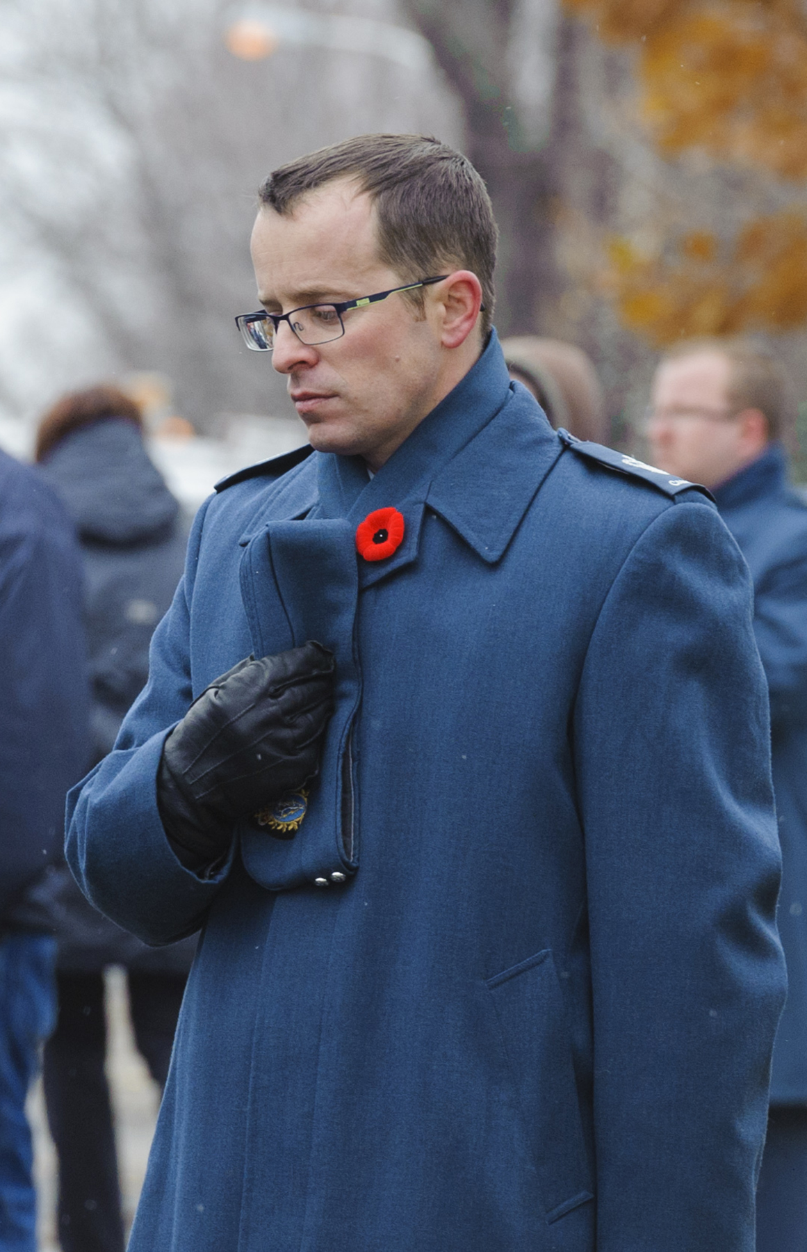 A uniformed man with a poppy on his blue topcoat bows his head and places his hand over his heart.