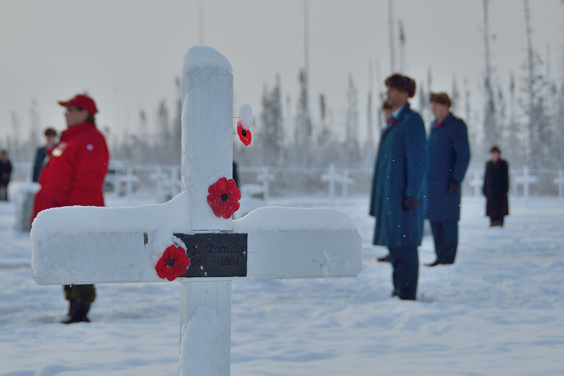 A cross adorned with poppies and new-fallen snow is one of many in 5 Wing Goose Bay, Newfoundland and Labrador's Commonwealth Cemetery, watched over by wing personnel and members of 5 Canadian Ranger Patrol Group during the Remembrance Day ceremony held on November 11, 2016. PHOTO: Master Corporal Krista Blizzard