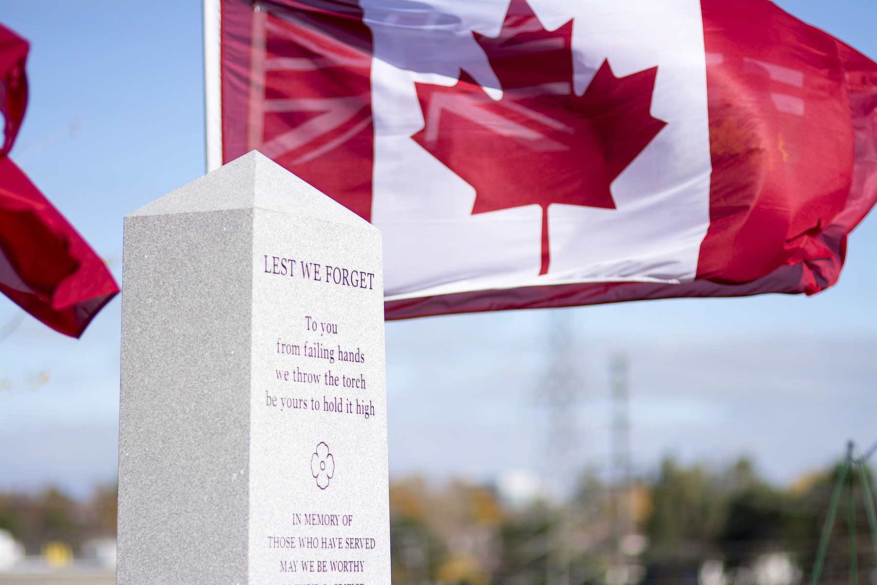 The Canadian flag snaps in a brisk wind beside the Seneca College cenotaph on the North York Newnham campus in Toronto, Ontario, during the November 11, 2016, Remembrance Day ceremony. PHOTO: Tai Nguyen, Seneca College