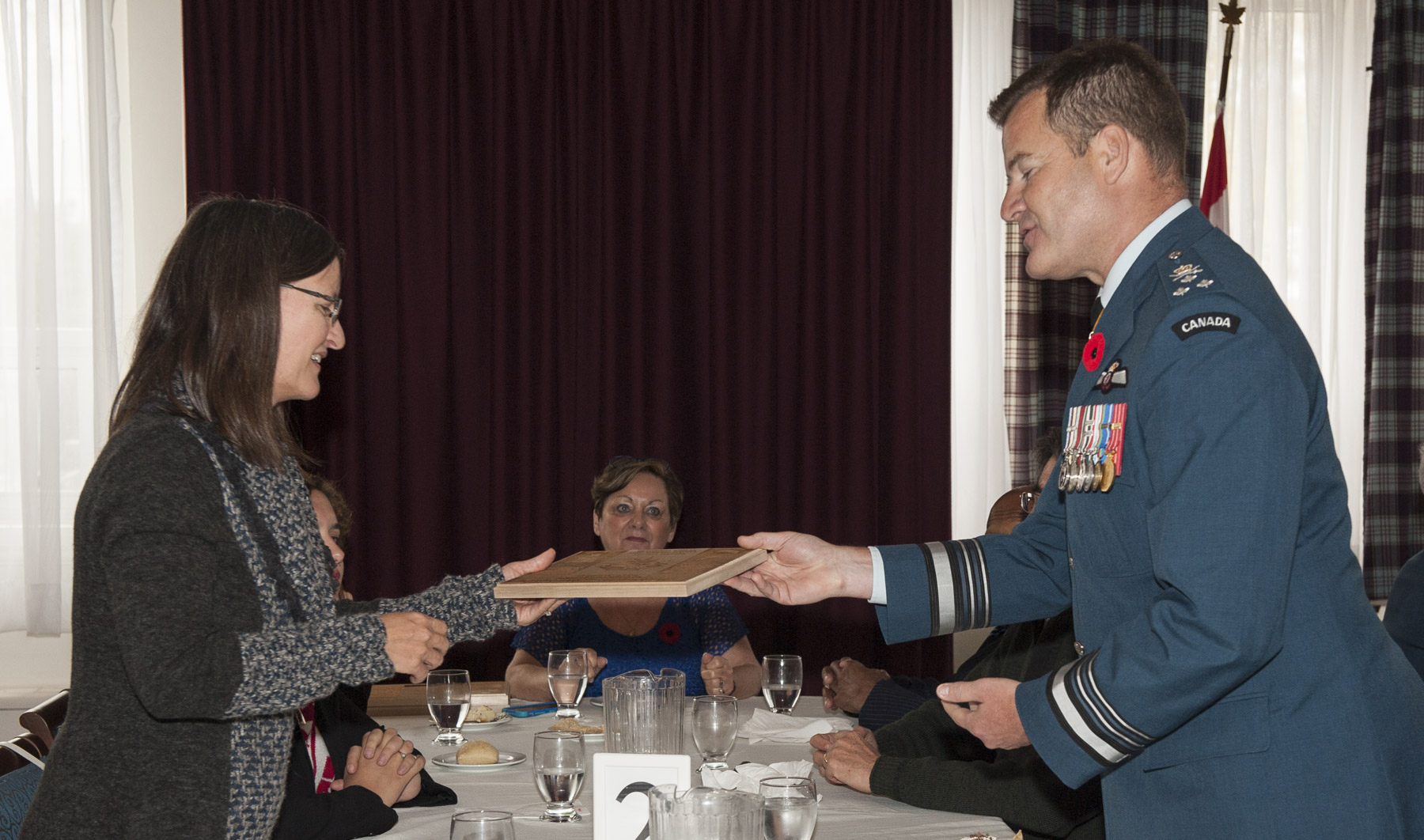 Lieutenant-General Mike Hood, commander of the Royal Canadian Air Force, gives a wooden plaque that replicates the plaque on the new Boxtop 22 commemorative cairn to Captain (retired) Wilma de Groot, who survived the Boxtop 22 crash on October 30, 1991. PHOTO: Corporal Audrey Solomon, TN02-2016-0807-012