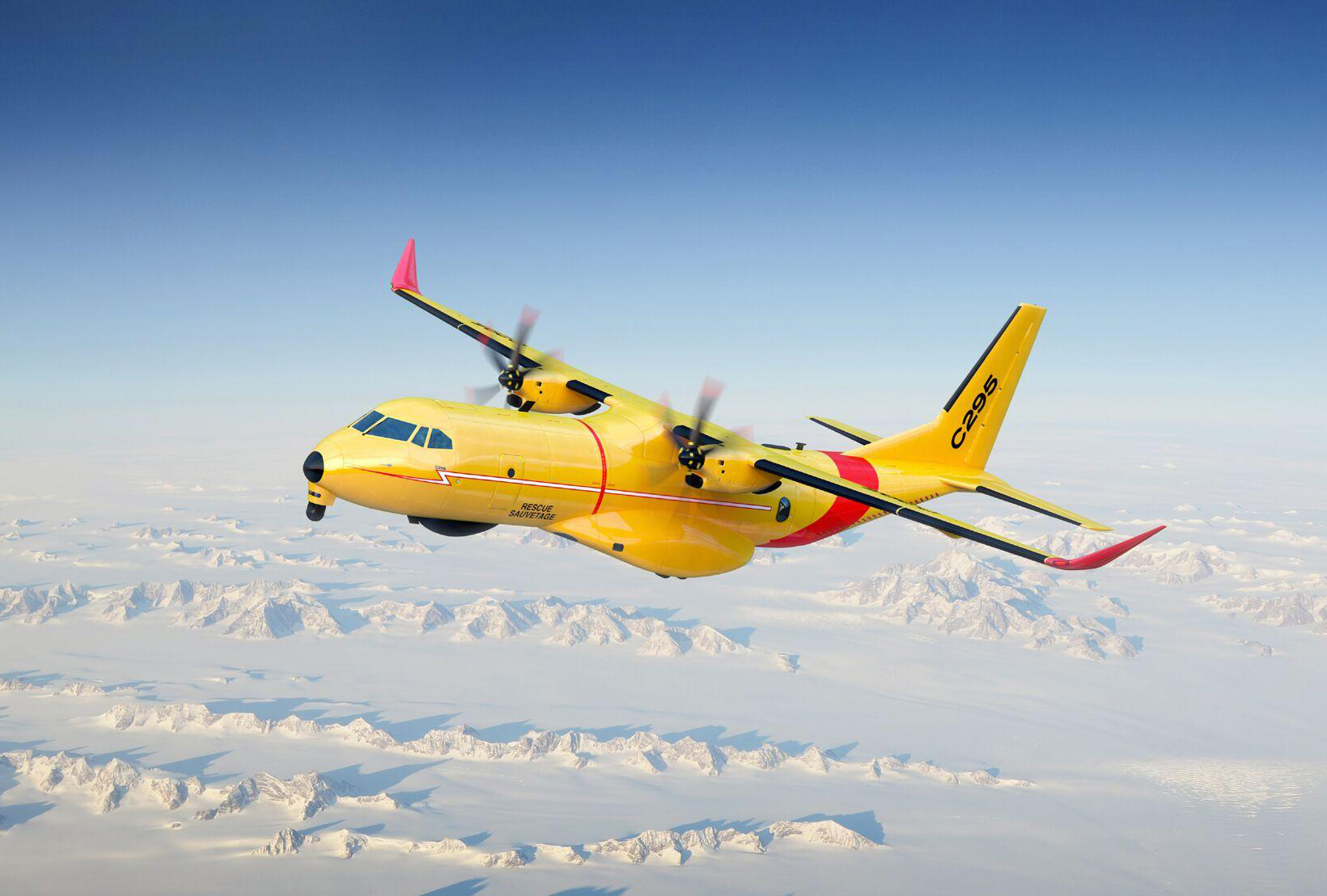 A large yellow aircraft flies over snow-covered terrain.