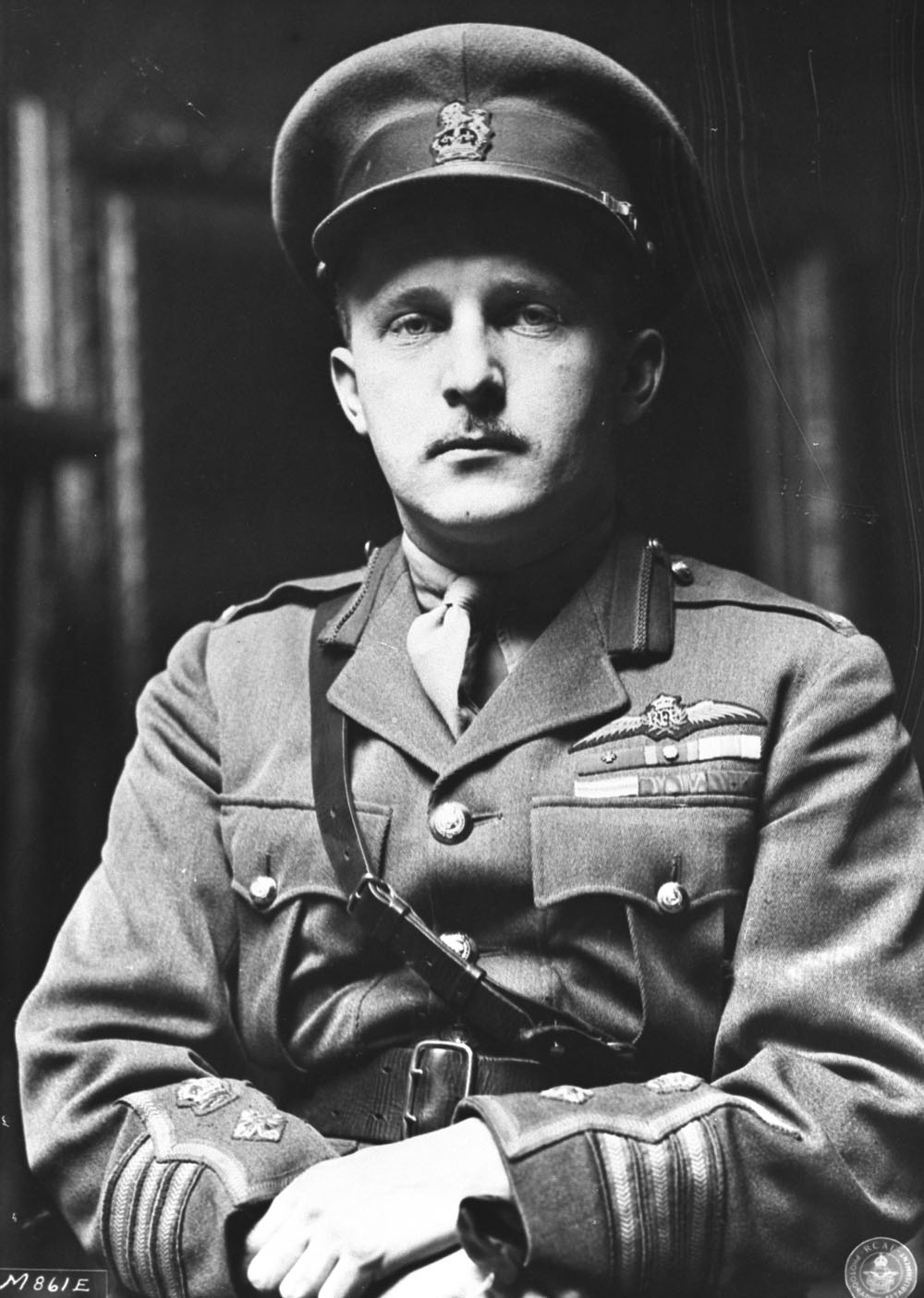 An old black and white photo of a seated man wearing a military uniform, looking at the camera.