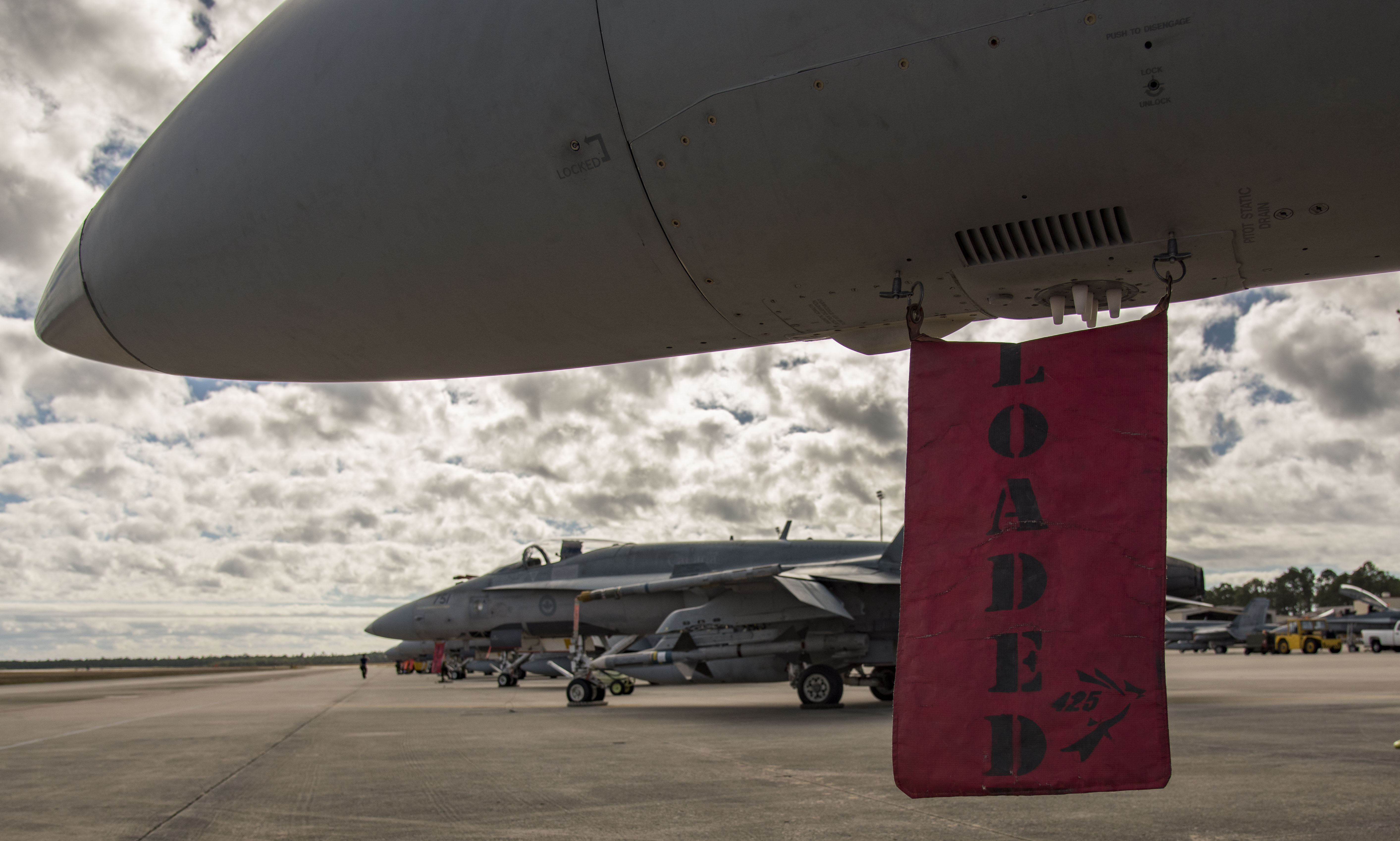 "A red flag with the word ""loaded"" written on it hangs from the underside of a fighter aircraft. Other fighter jets are lined up on the tarmac in the background."