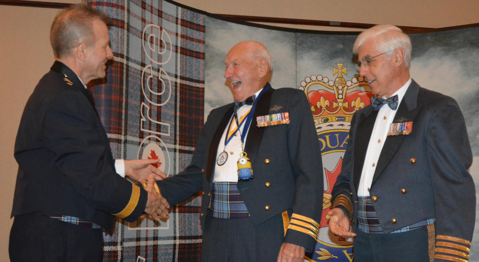 "Major-General William Seymour congratulates Lieutenant-Colonel (retired) Syd ""Cyclops"" Burrows on his induction to the newly-created and very informal ""Order of Kevin"" during the Royal Canadian Air Force Association's annual awards banquet in October 2016. Colonel (retired) Terry Chester, national president of the Association, stands by to offer his congratulations. Lieutenant-Colonel Burrows, like Kevin the Minion, has only one eye – the result of a bird strike while he was flying an F-86 Sabre in Europe in the 1950s. PHOTO: Lieutenant-Colonel (retired) Dean Black, RCAFA"