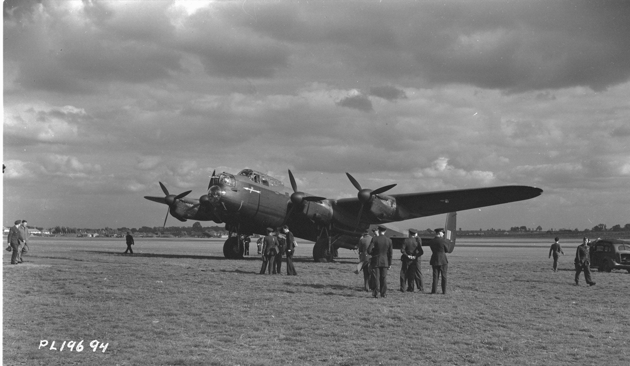In an undated photograph, aircrew and groundcrew of the RCAF and the RAF welcome the first Canadian built-Lancaster bomber as it taxies off the runway at a London drome. PHOTO: DND Archives, PL-19694