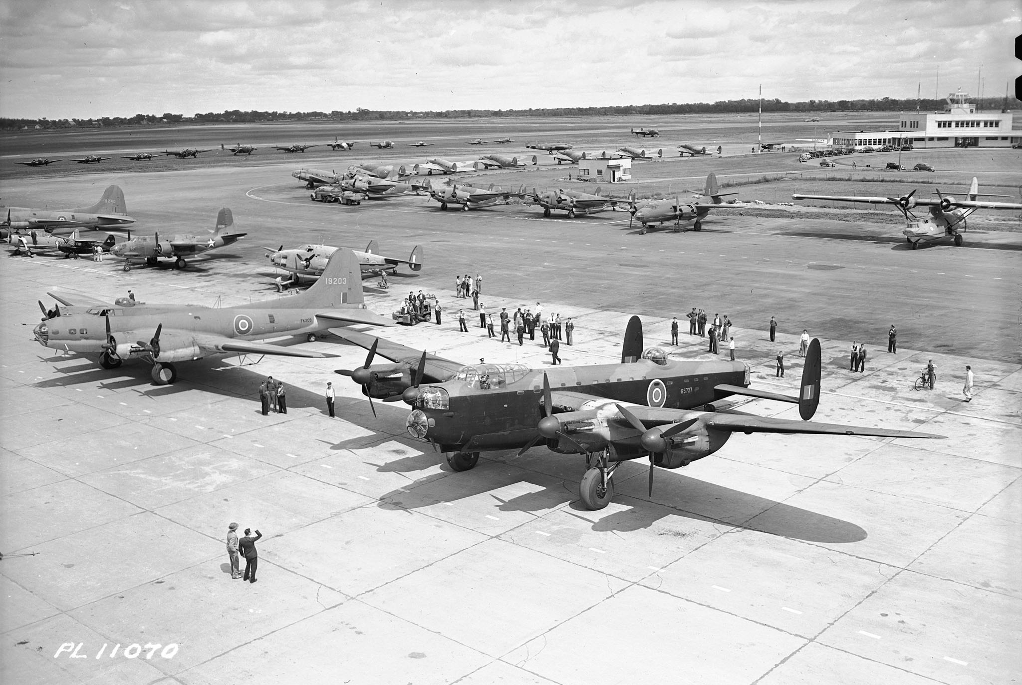 On August 24, 1942, at Montreal, Quebec's Dorval Airport, RCAF personnel and guests get a close-up view of the huge Lancaster bomber being built in Canada – the aircraft that Royal Canadian Air Force crews fly night after night to smash at the industrial centres of the Third Reich. PHOTO: DND Archives, PL-11070