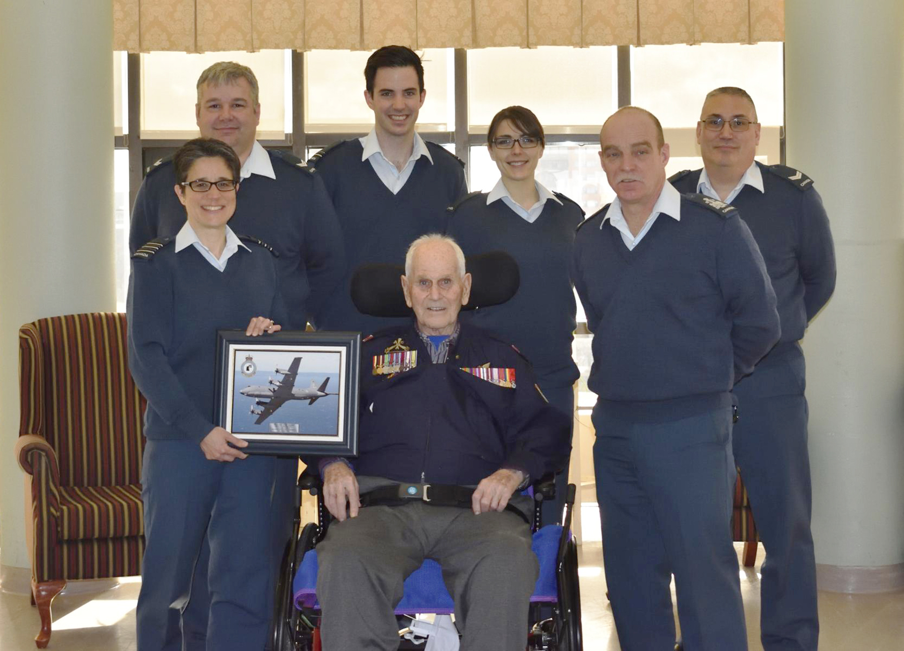 Lieutenant-Colonel (retired) Russell Hubley, DFC, CD (seated) and, from left to right, 405 (Long Range Patrol) Squadron Commanding Officer Lieutenant-Colonel Marie-Claude Osmond, and squadron members Corporal Timothy Joice, Lieutenant Evan Fay, Aviator Sarah Poulin, Squadron Chief Warrant Officer Craig Chislett, and Corporal Don Kirkwood, gather for a photograph on January 31, 2017, at Camp Hill Veterans Hospital in Halifax, Nova Scotia. PHOTO: Corporal Don Kirkwood