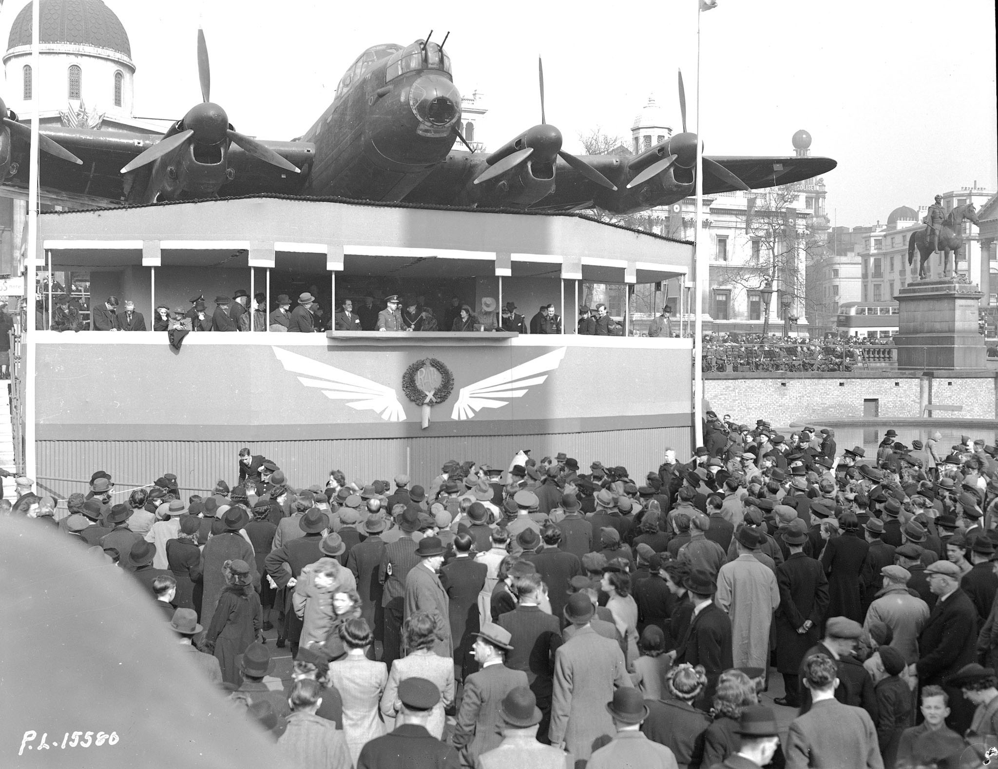 "On March 13, 1943, under the nose of a giant Lancaster bomber, Air Marshal Harold ""Gus"" Edwards, air officer commander-in-chief, RCAF Overseas, addresses a large gathering in Trafalgar Square in London, England, at the conclusion of a successful Wings for Victory campaign. PHOTO: DND Archives, PL-15580"