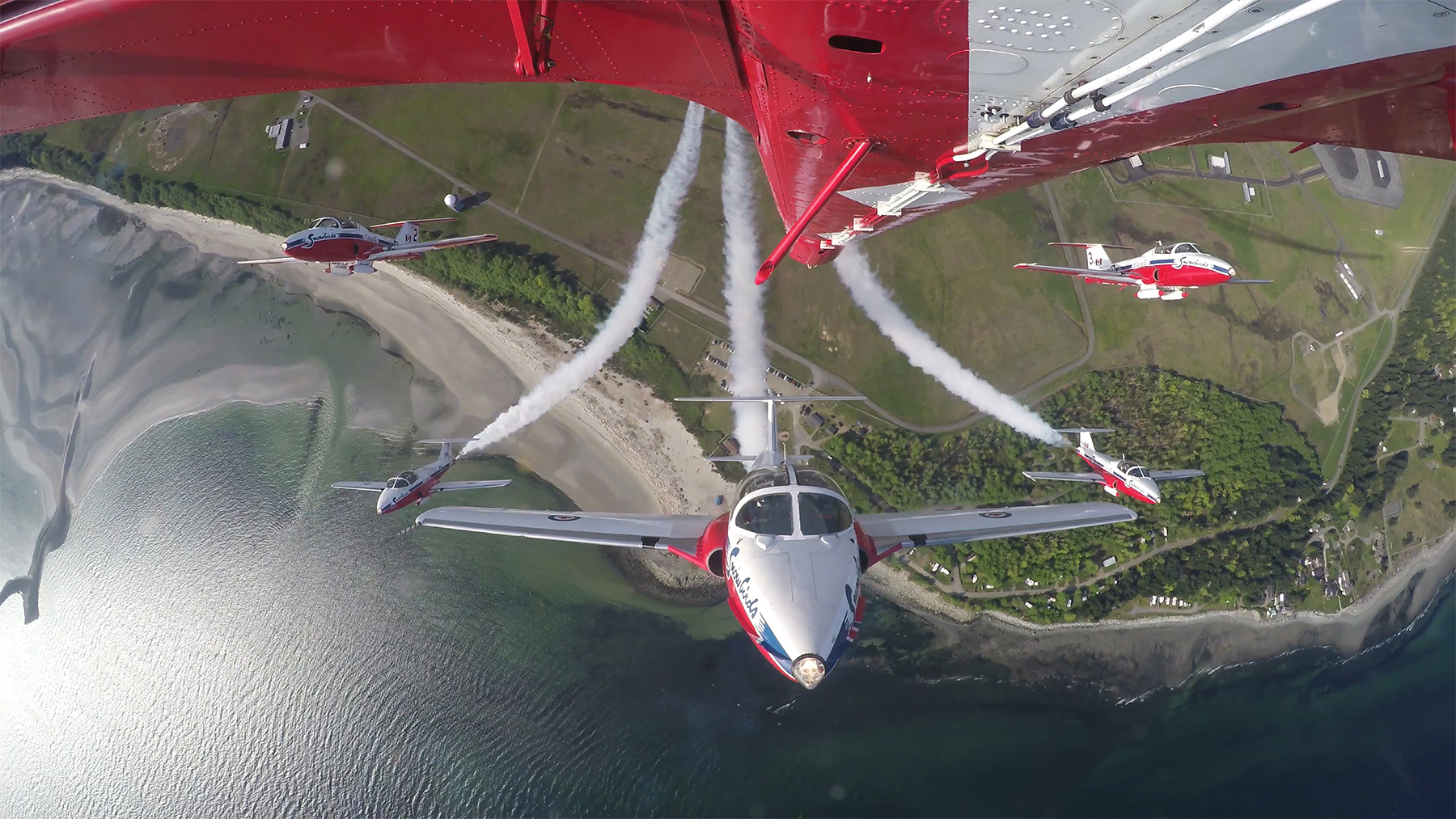 In a vertical climb over the shoreline of British Columbia in April 2015, the Snowbirds air demonstration team is filmed by the TankCam, mounted on the belly of the Team Lead's aircraft, the tail of which can be seen here across the top of the photo. PHOTO: Snowbirds TankCam