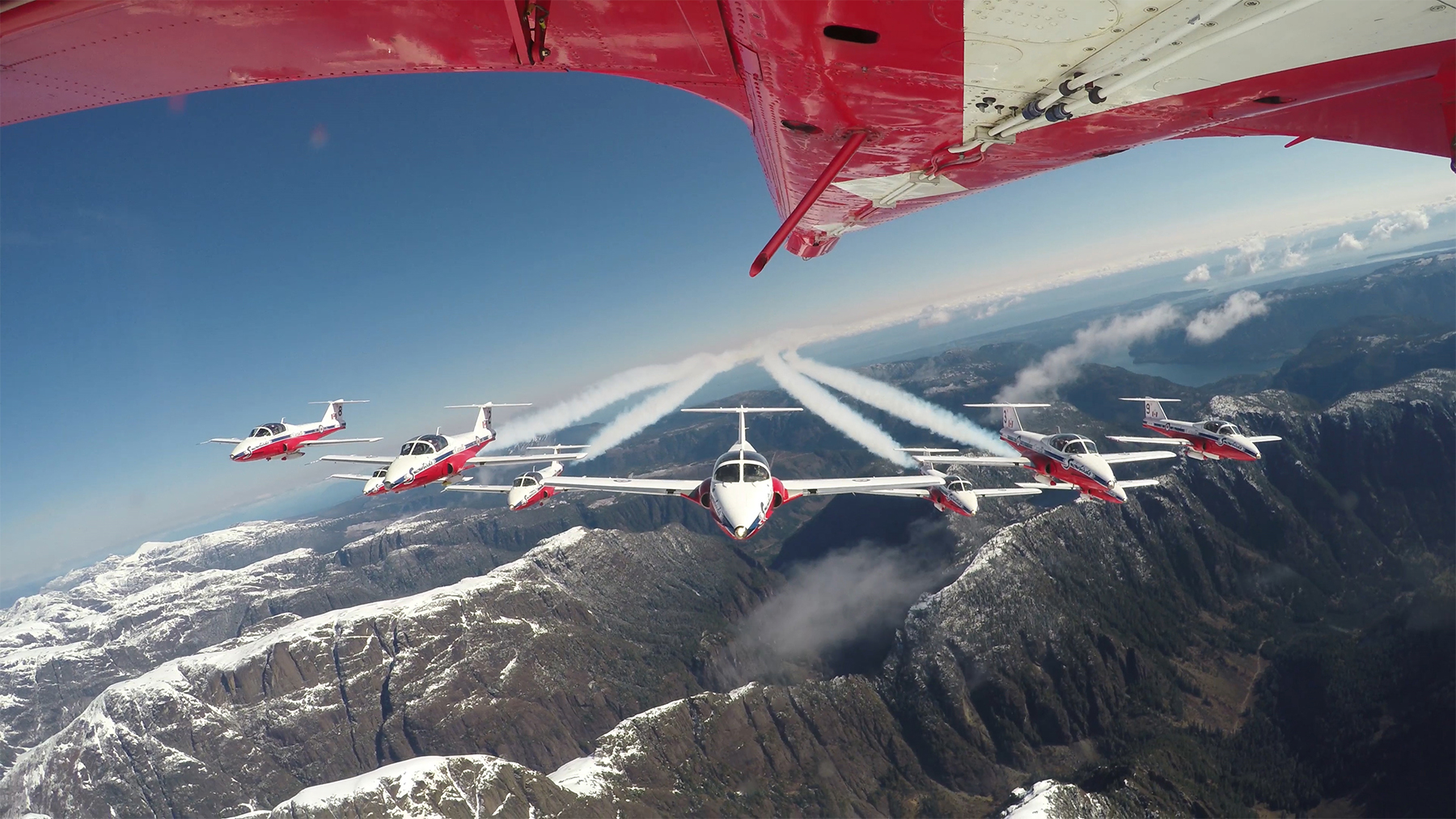 Practising over the mountains of British Columbia in April 2015, nine Royal Canadian Air Force Snowbirds are captured by the TankCam mounted on the belly of the Team Lead's aircraft. PHOTO: Snowbirds TankCam