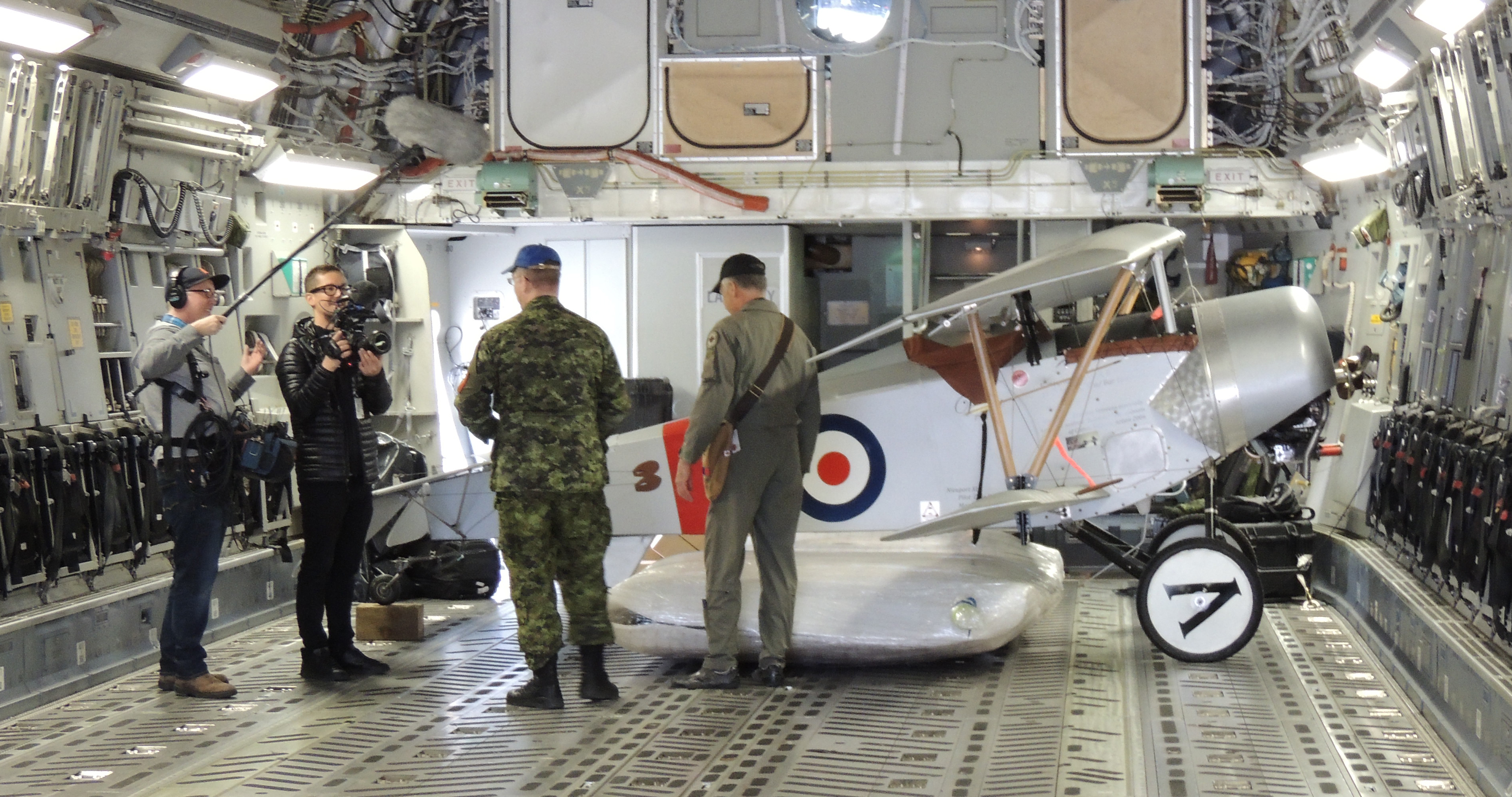 A Nieuport XI rests inside the CC-177 Globemaster III from 429 Transport Squadron, located at 8 Wing Trenton, Ontario, as crew speak with reporters. PHOTO: Major Holly-Anne Brown