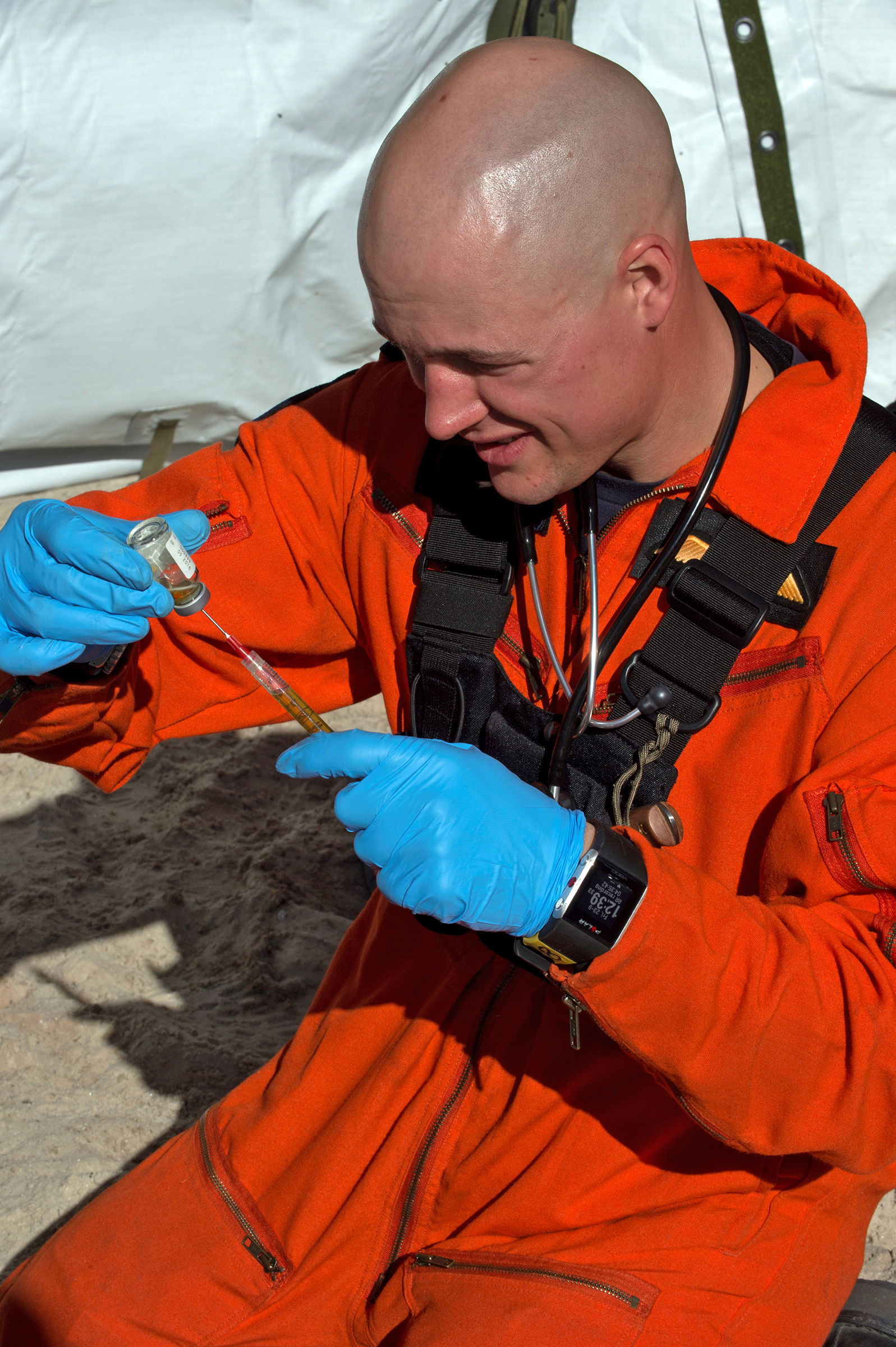 A man with a shaved head, wearing an orange jump suit and blue gloves, fills a syringe from a small vial of liquid.