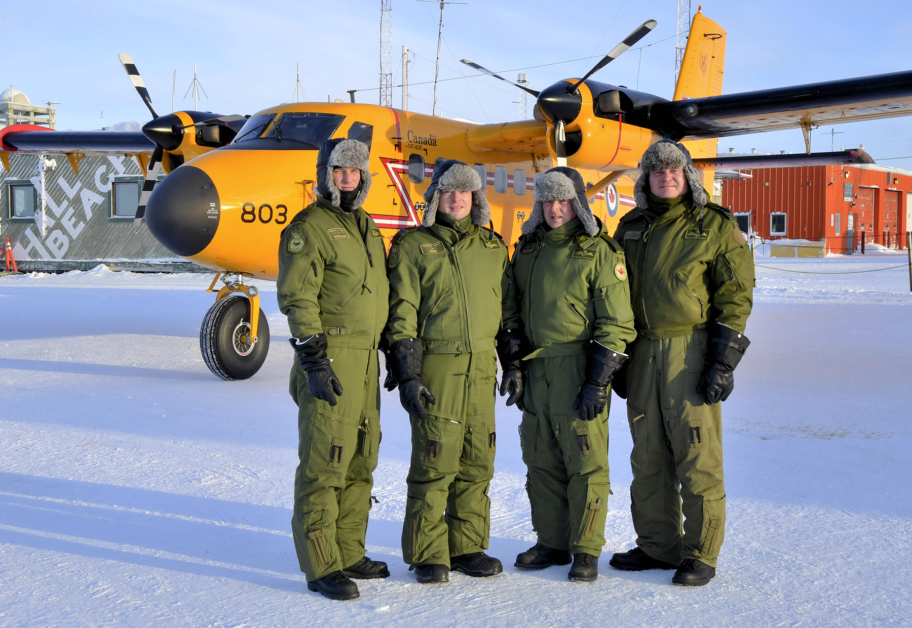 Four men in green Arctic wear stand in snow beside a small yellow aircraft.