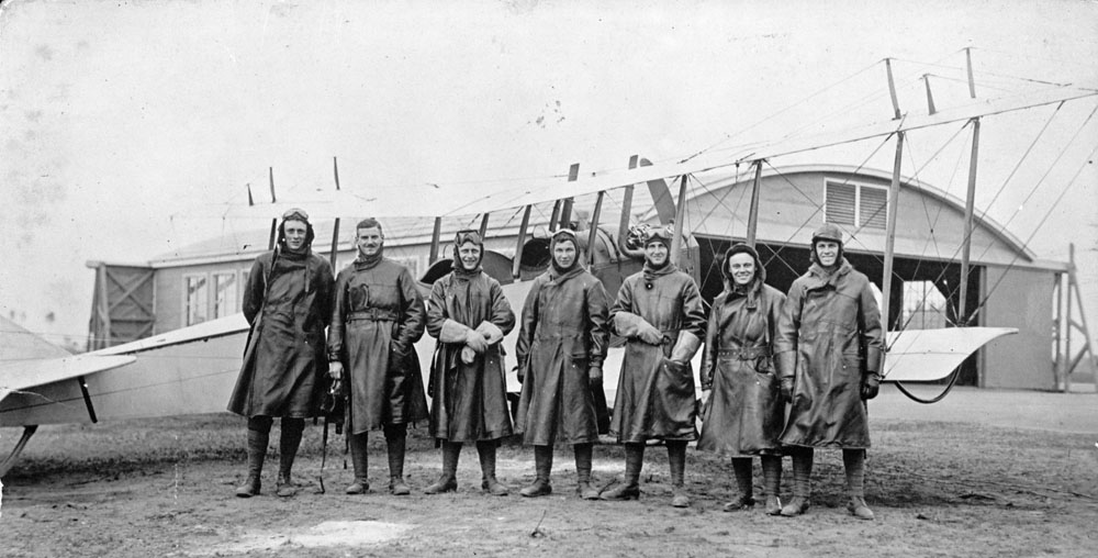 An old black and white photo of seven men standing in front of a biplane.