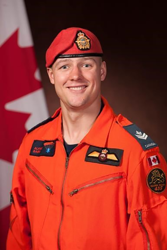 A man in an orange coverall and beret sits beside a red and white flag.