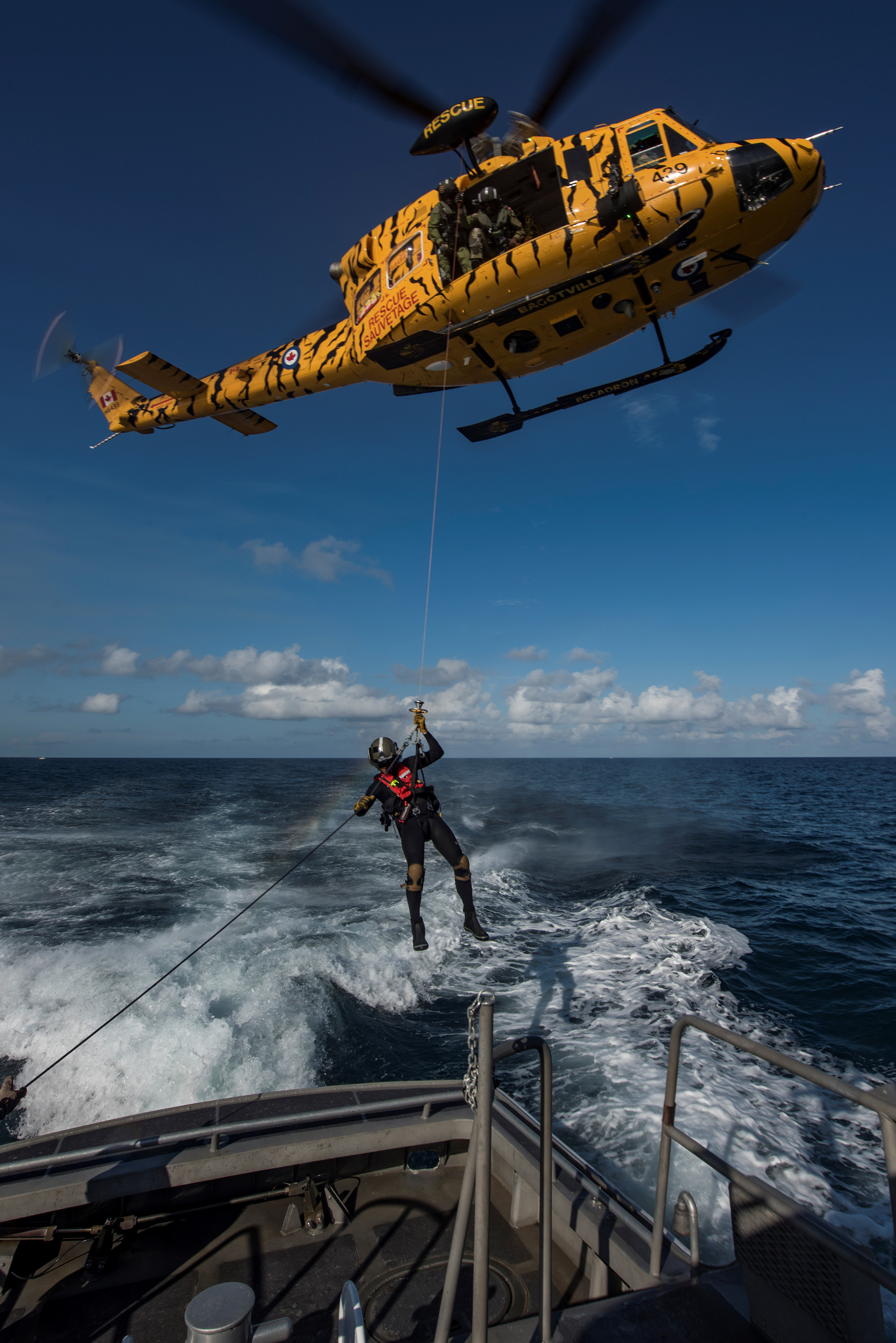 A search and rescue technician is lowered from A CH-146 Griffon helicopter onto a simulated vessel in distress off the coast of Miami, Florida, during Exercise Southern Breeze on February 7, 2017. PHOTO: Corporal Bryan Carter, CK04-2017-0062-010