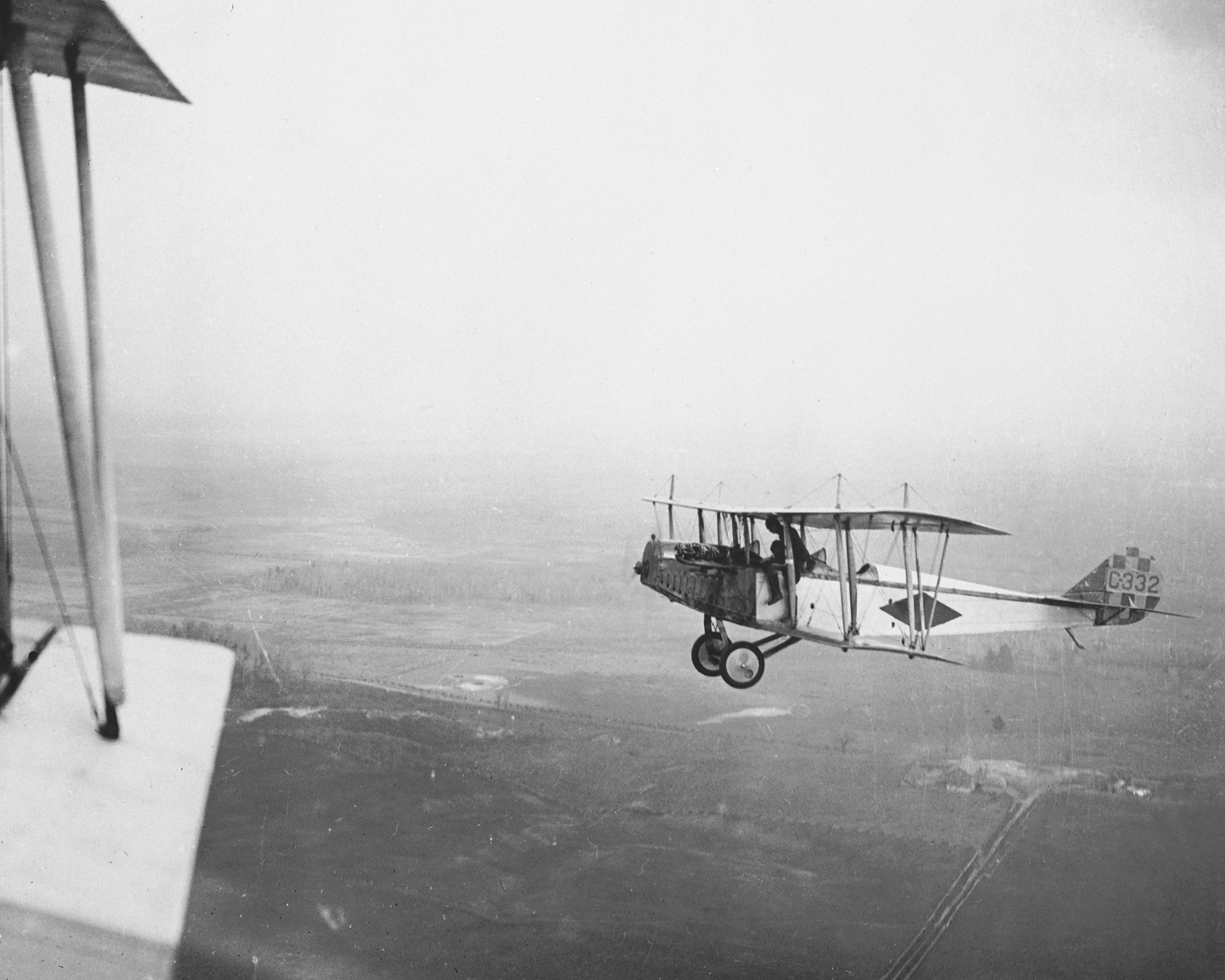 "Two Royal Flying Corps Canada airmen, one having climbed out of his seat to straddle the side of the forward cockpit, chat about stability while in flight in their Curtiss JN-4 ""Canuck"" trainer – No. C332.  PHOTO: DND Archives, RE-19067-9"