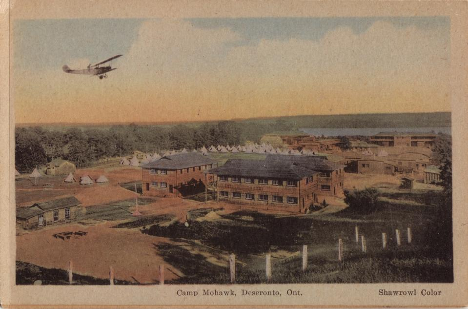 "An undated postcard shows a Curtiss JN-4 ""Canuck"" trainer aircraft overflying Camp Mohawk, near Deseronto, Ontario, IMAGE: Deseronto Archives, https://deserontoarchives.wordpress.com"