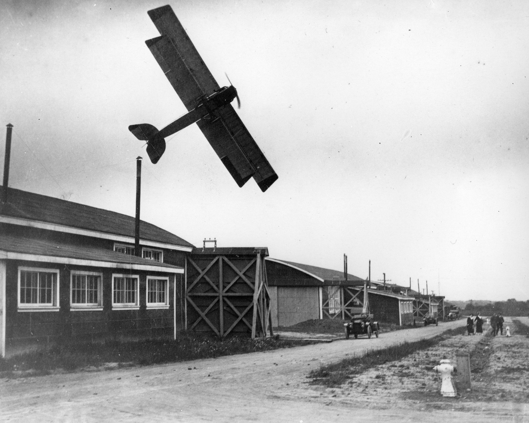 In a black and white photograph, a vintage bi-plane flies extremely low over one-storey wooden buildings.