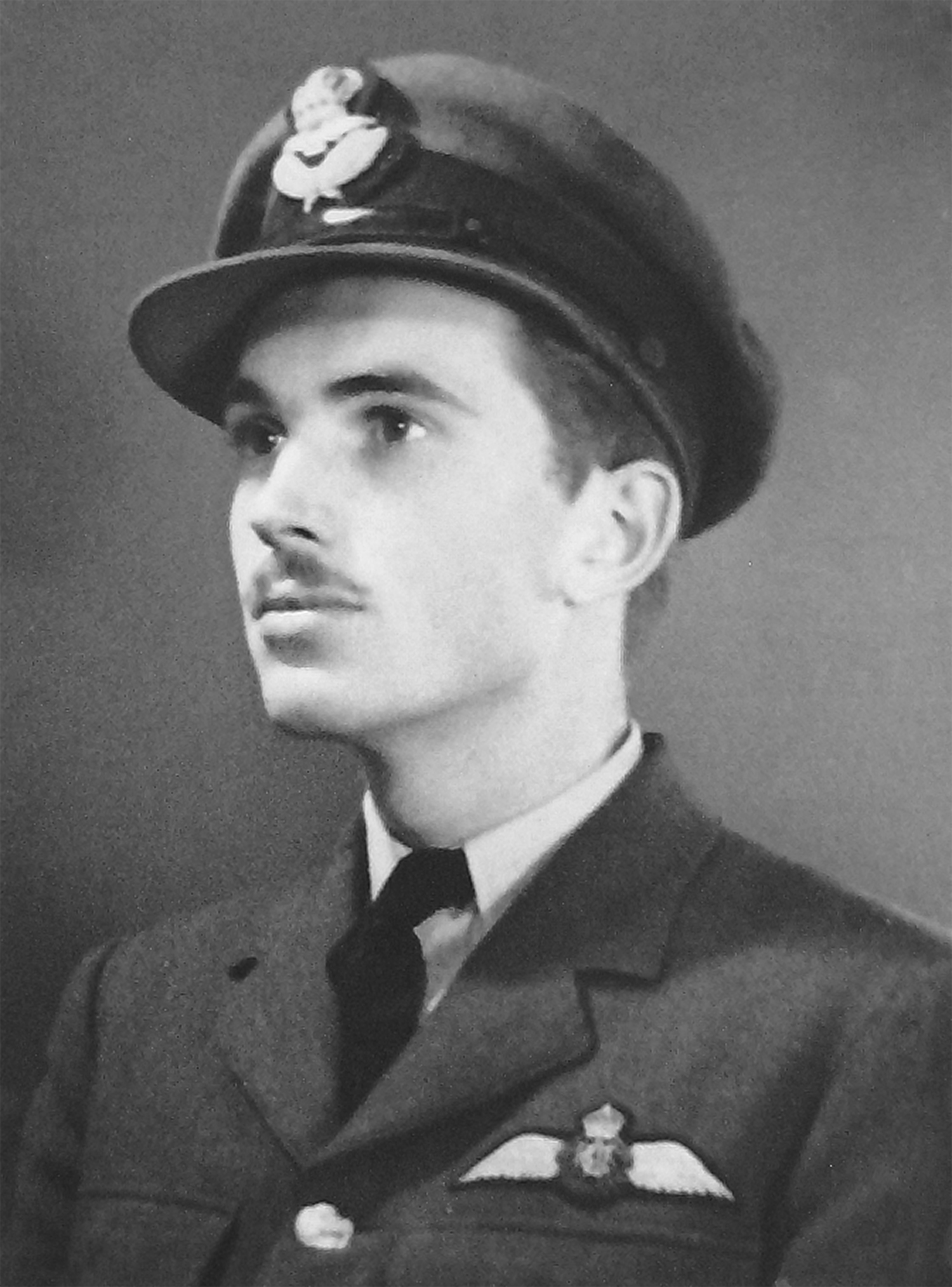 A head and shoulders, black and white photo of a young man in a military uniform, wearing a hat, with pilot's wings over his left tunic pocket.