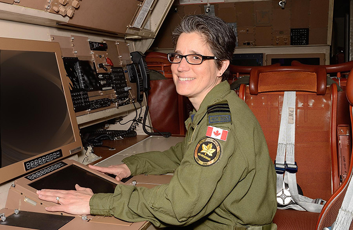 slide - A woman in a green flight suit sits at a desk in an aircraft.