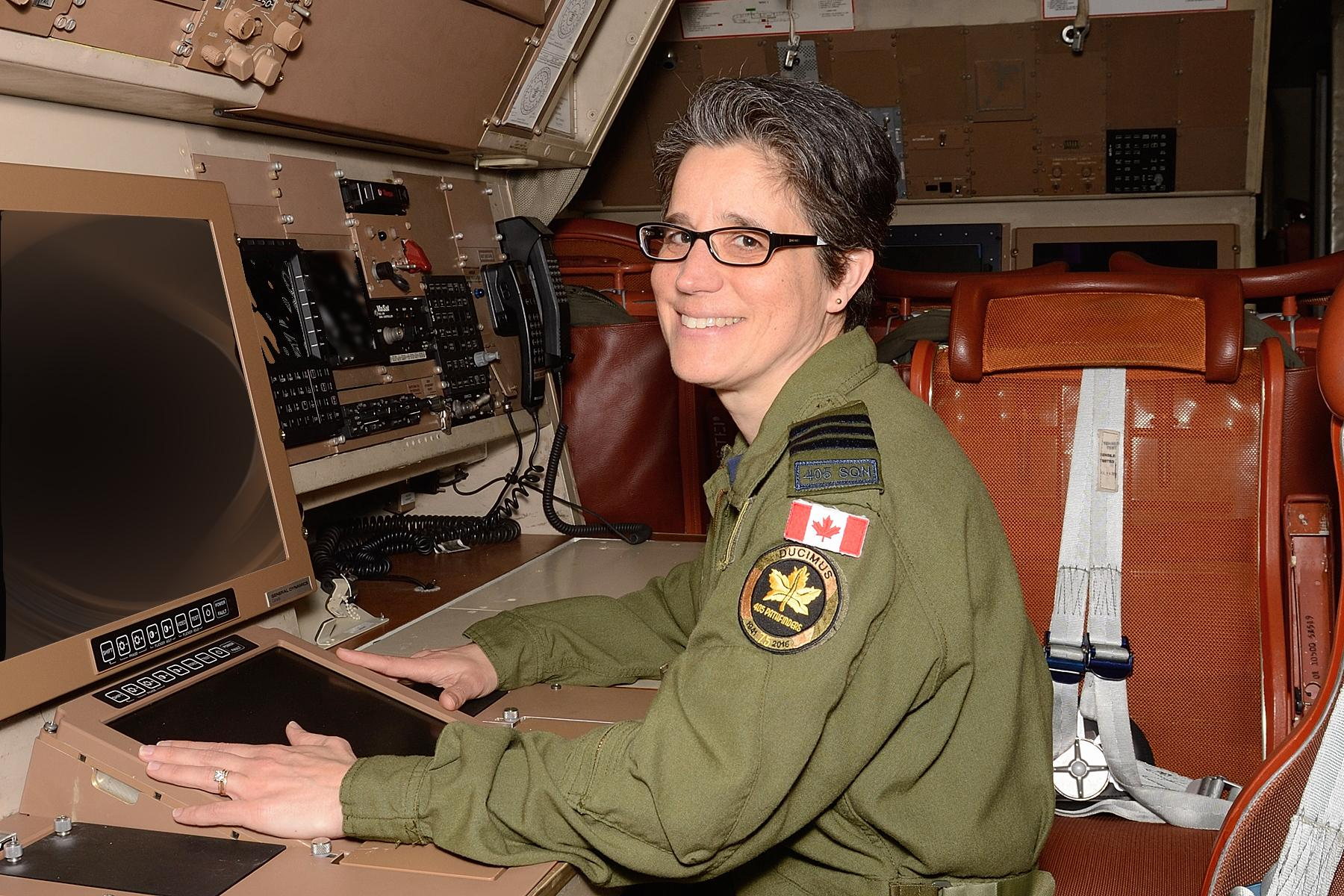 A woman in a green flight suit sits at a desk in an aircraft.