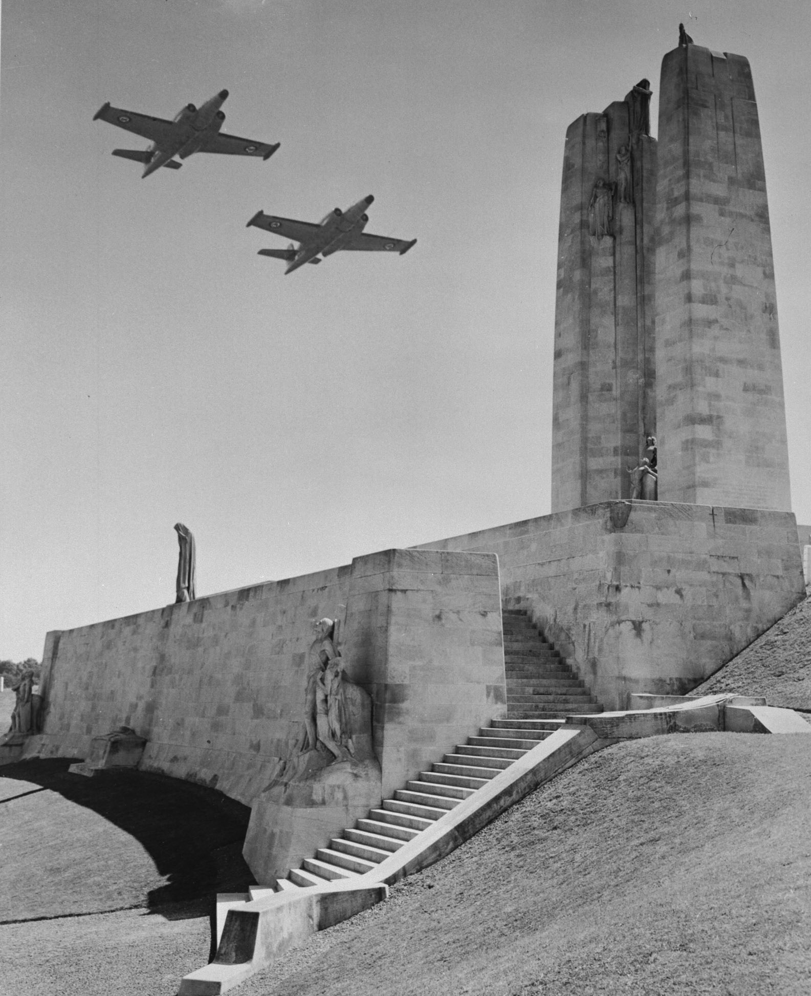 A black and white photo of two fighter aircraft flying close to a large white monument on a hillside.
