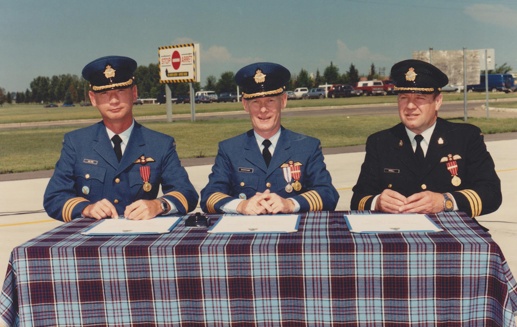 Atop the traditional drape of Royal Canadian Air Force tartan, Lieutenant-Colonel Chris Colton (left), incoming commanding officer of 440 Transport Squadron, and Lieutenant-Colonel Barry Krall (right), outgoing commanding officer of the squadron, flank Colonel Bill Buckham, 18 Wing Edmonton commander, during the squadron's 1987 change of command ceremony. Lieutenant-Colonel Krall wears the recently phased out tru-service uniform, while the others wear the new. PHOTO: DND