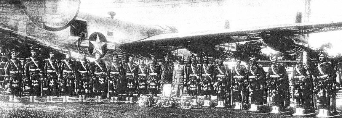 Members of the Royal Canadian Air Force Pipe Band gather beside a Boeing B-17 Flying Fortress while on a visit to Detroit, Michigan, during the Second World War. From left are James Ross (London, Ontario); Frank MacKenzie (Lucknow, Ontario); Jim Murphy (St. Catharines, Ontario); Les Hutchinson (Ingersoll, Ontario); unidentified piper, Biff Andrews (Clinton Ontario); Bert Ross (London Ontario); Jack Graham, Sandy Russell, Jack Gair, and Weary Wile (all from Winnipeg, Manitoba); Flying Officer Herbertson (Toronto, Ontario); Wally Simpson (Winnipeg, Manitoba); George Fairlie (Windsor, Ontario); Ken Stuebing (Kitchener, Ontario); Donald Fletcher (Lachute, Québec); Bill Mutch (Clinton, Ontario); Jack Smithson (Kitchener, Ontario); Harry Forgie (Winnipeg, Manitoba); and Tom Carroll (Kitchener, Ontario).