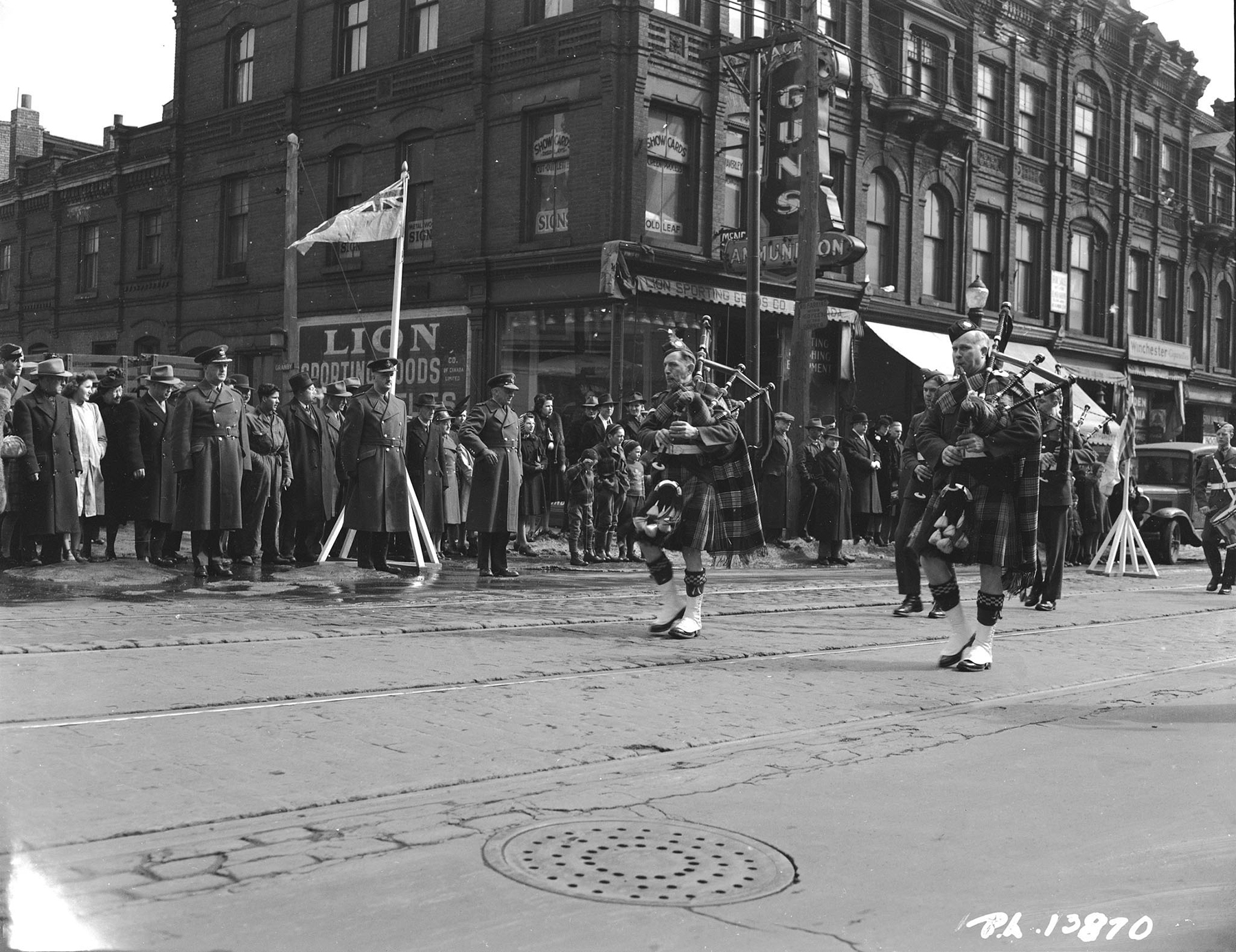 In full RCAF tartan regalia, the No. 9 Service Flying Training School Pipe Band from Centralia, Ontario, parades past Air Commodore G.E. Wait as he takes the salute on March 13, 1943, in Toronto, Ontario. The band was leading Royal Canadian Air Force airmen from Toronto`s No. 1 Manning Depot to Maple Leaf Gardens for a hockey playoff game between the Air Force and a team representing the Royal Canadian Navy. PHOTO: DND Archives, PL-13870