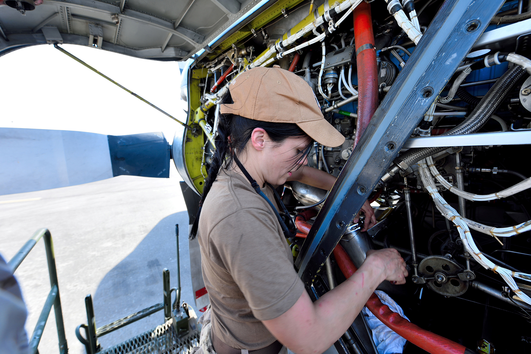 An aviation technician performs general maintenance on a CP-140 Aurora engine in Kuwait on April 4, 2016, during Operation Impact. PHOTO: Op Impact, DND, KW03-2016-0077-001