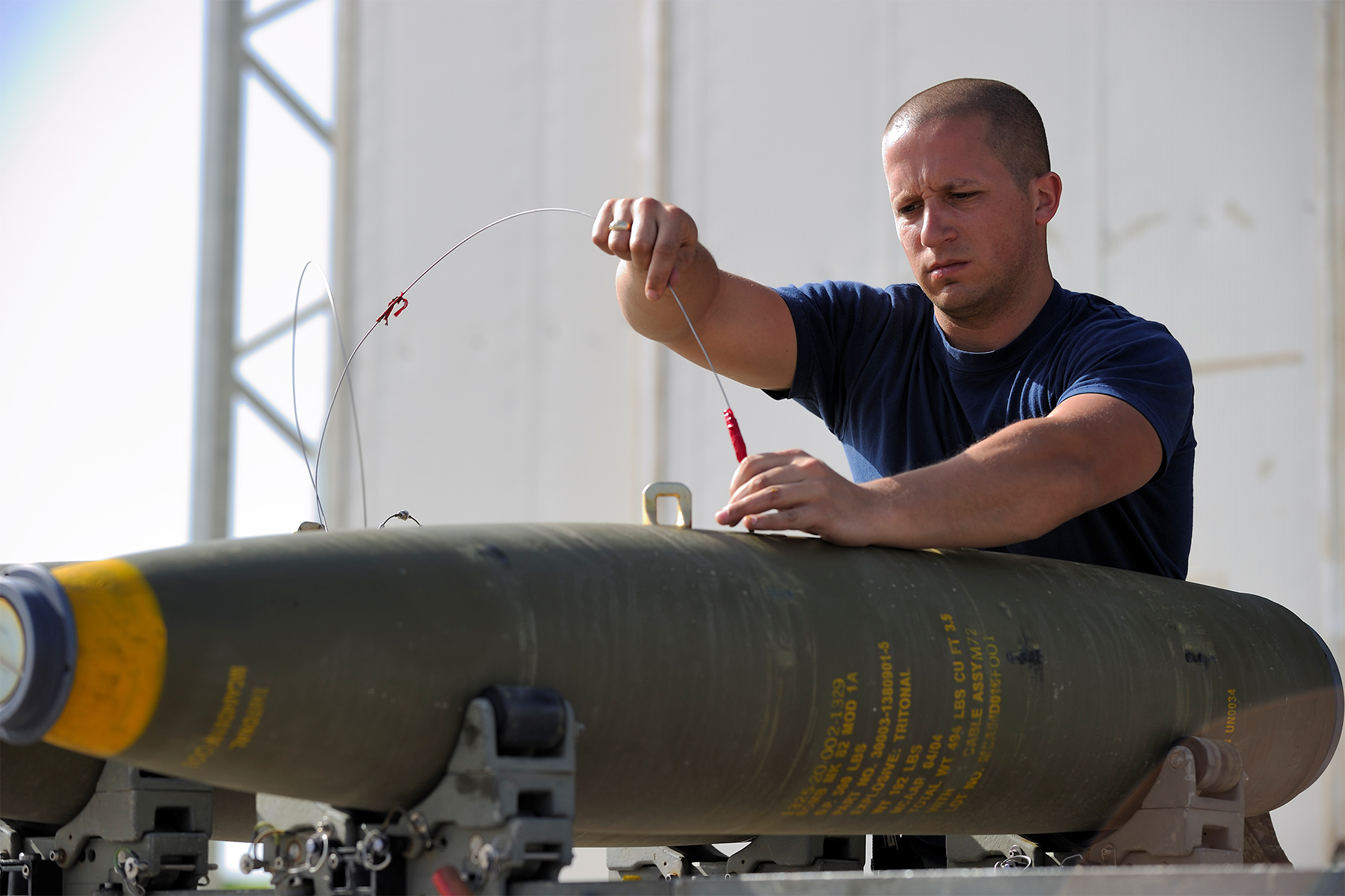 An air weapons technician from 3 Wing, Bagotville, Québec's 425 Tactical Fighter Squadron assembles a laser-guided GBU-12 bomb in Trapani, Italy, on April 4, 2011. PHOTO: Corporal Marc-André Gaudreault, IS2011-6002-1364