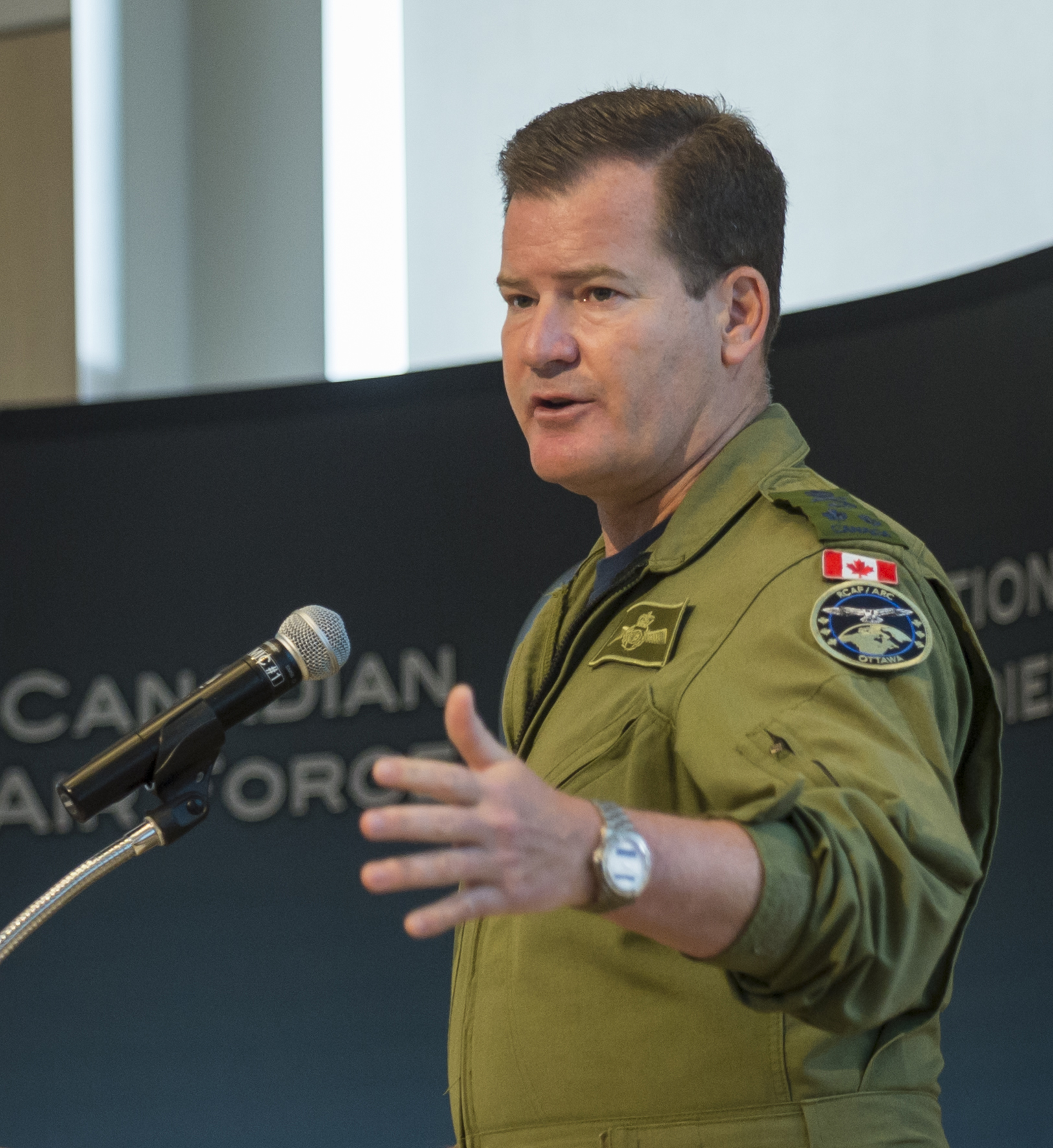 A man wearing an olive green flight suit speaks from behind a podium while gesturing with his left hand.