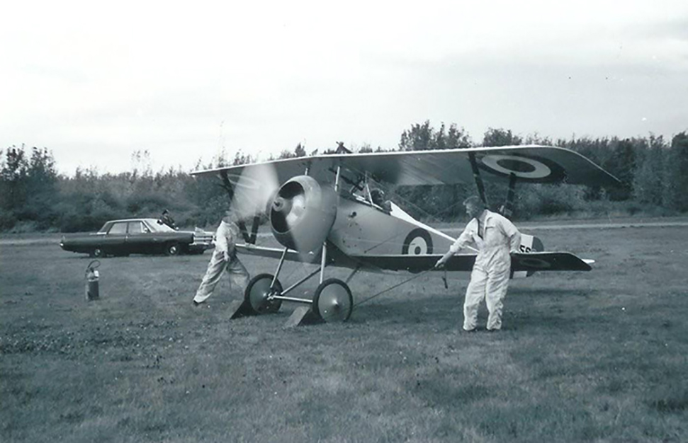 "With Flight Lieutenant Bill Long in the cockpit and Danny Jones (foreground) and another ground crew member about to pull out the chocks, the National Aeronautical Collection's replica Nieuport 17 warms up at RCAF Station Rockcliffe in 1967. In the background, the driver of a flagged RCAF staff car waits. Perhaps a general officer was there to witness and approve the display. This Nieuport 17 was built by American amateur airplane-maker Carl R. Swanson in 1961 as a flying replica. A generous donor purchased the aircraft for the Museum in 1963. It was refinished to match the airplane in which the famous Canadian ace William Avery ""Billy"" Bishop earned the Victoria Cross. Wing Commander Paul Hartman took the aircraft on its first flight in May 1967. PHOTO: Bill Ewing"