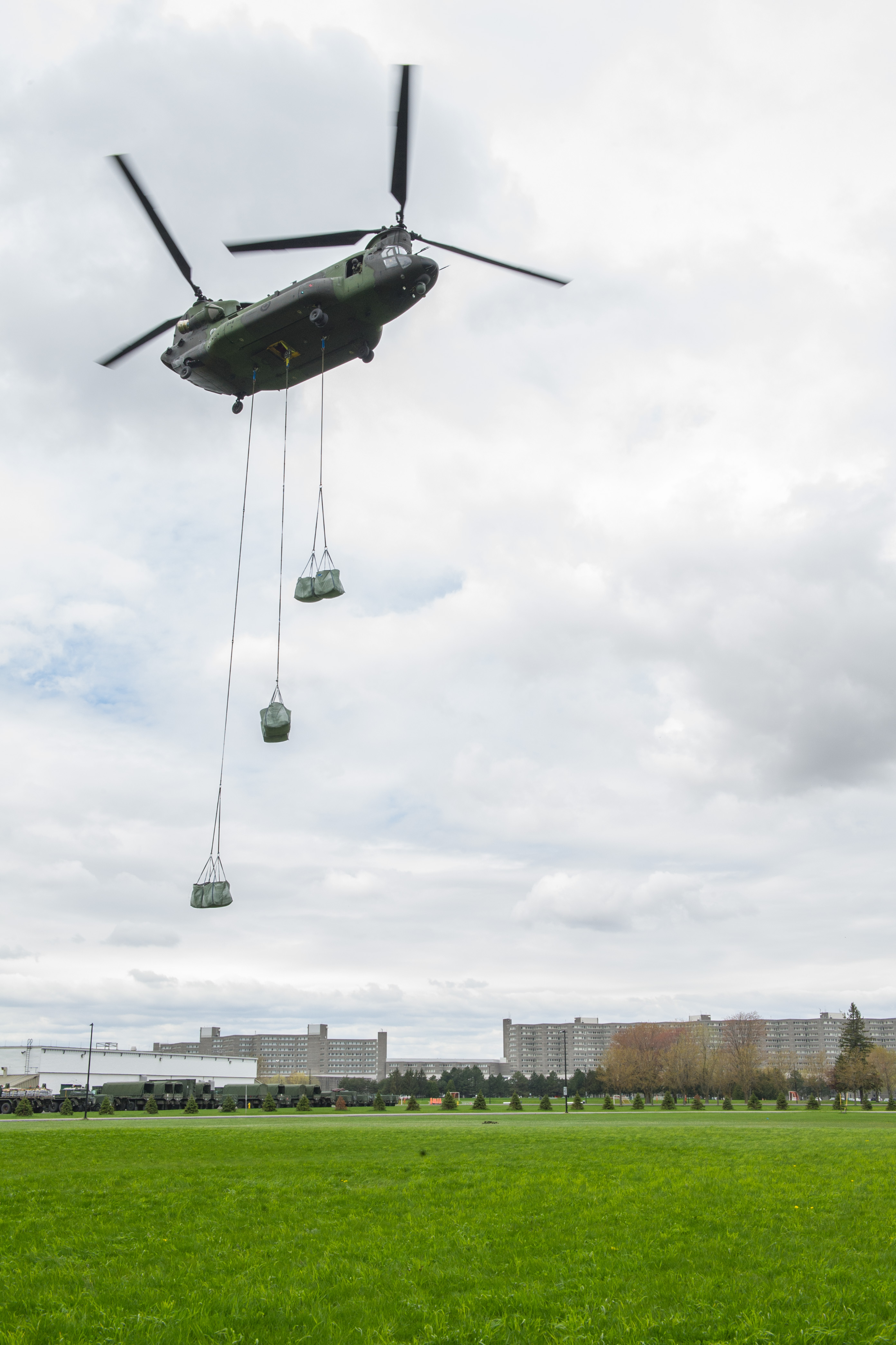 A CH-147 Chinook of 430 Tactical Helicopter Squadron, deployed as part of Operation LENTUS, flies over St-Jean garrison with sandbags to flooded areas to distribute to the disaster victims, The HD-4 building of St-Jean Garrison, Quebec, Canada, May 10, 2017.Photo: MSM Anne-Marie Brisson