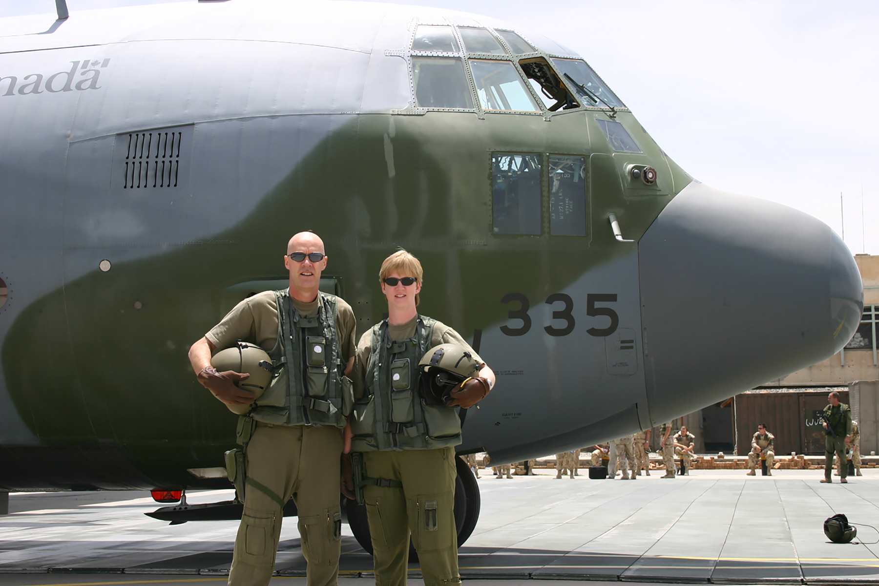 "A woman and man in uniform, holding helmets, stand beside the nose of a large aircraft with ""335"" on its nose."
