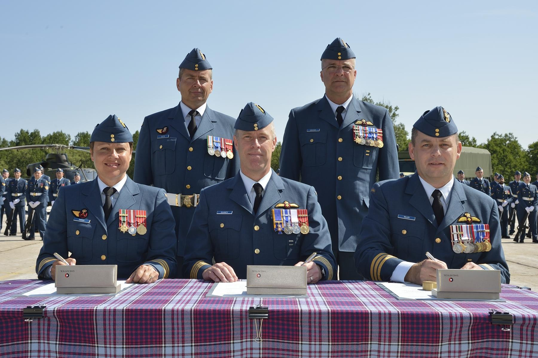 Lieutenant-Colonel Jill Bishop takes command of 400 Tactical Helicopter Squadron from Lieutenant-Colonel Dave Miller at a ceremony held in Borden on July 15, 2015. Colonel Scott Clancy, centre, commander of 1 Wing to which 400 Squadron reports, presided over the ceremony. In the back row are Master Warrant Officer Yvan Coté (left), 400 Squadron's acting squadron chief warrant officer and Chief Warrant Officer Jacques Boucher, 1 Wing's chief warrant officer. PHOTO: DND, BM2015-0094-42