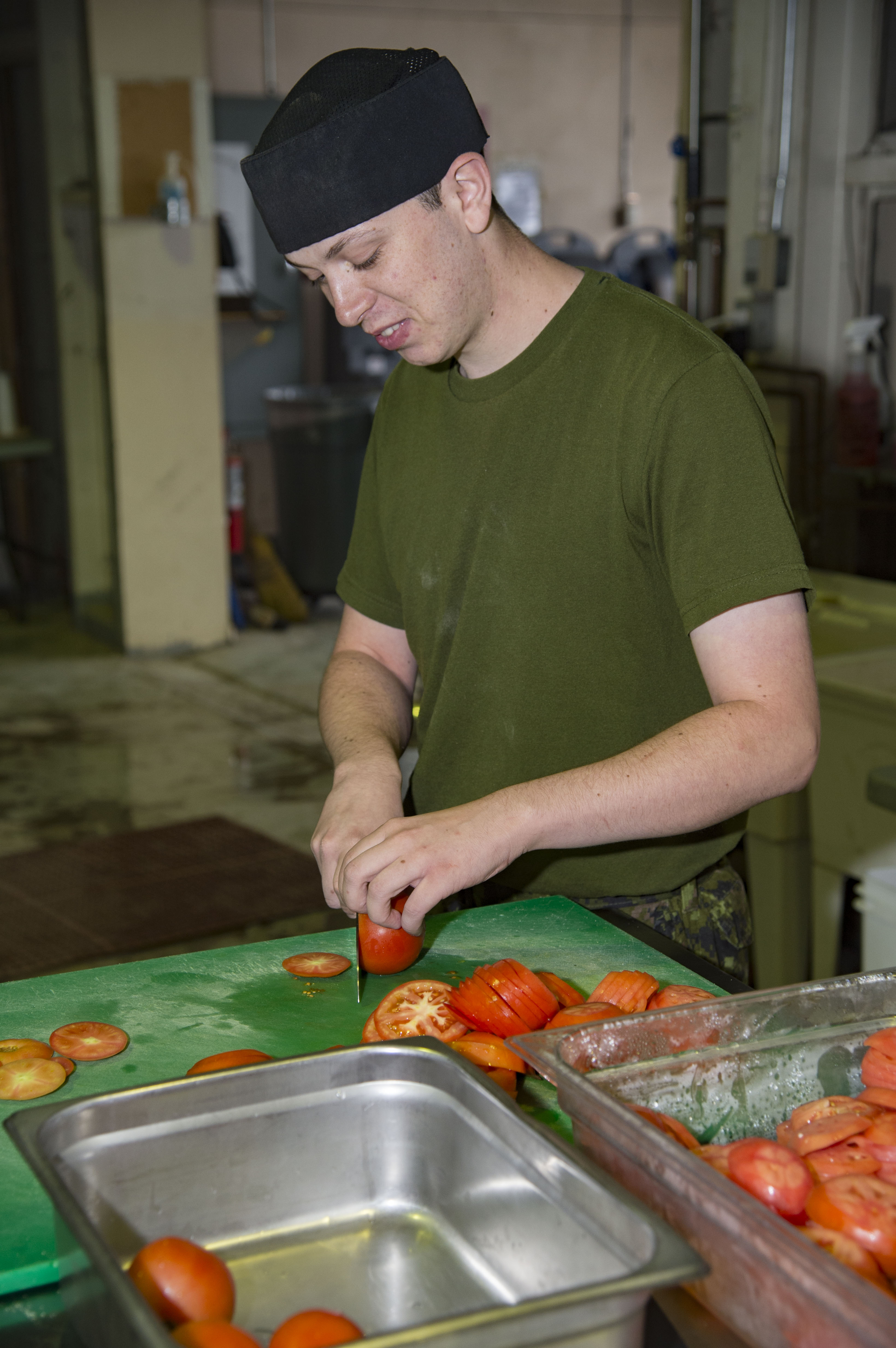 A man in green T-shirt and a black cap slices tomatoes.