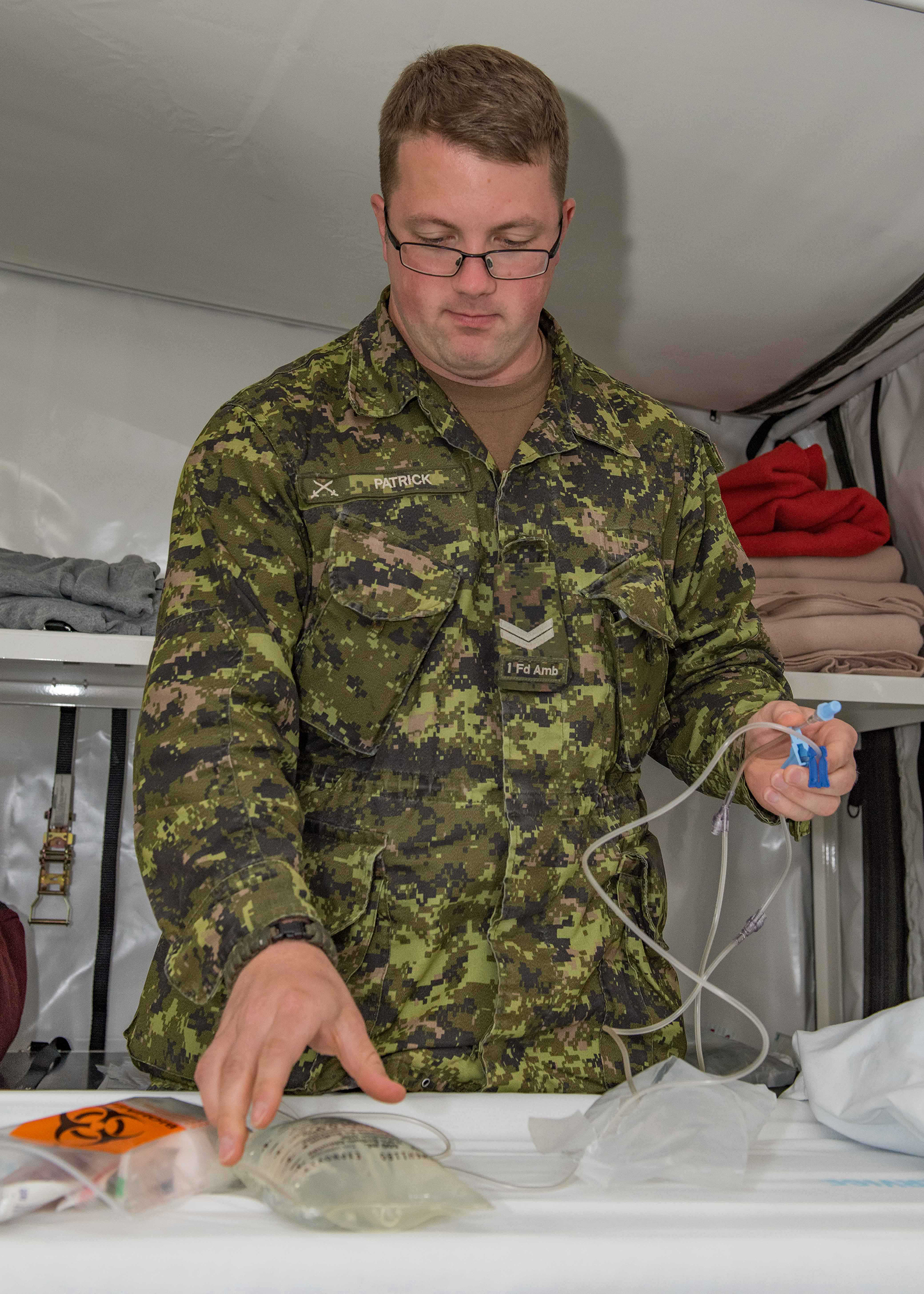 Corporal Sean Patrick, a medical technician with 1 Field Ambulance in Edmonton, Alberta, prepares intravenous fluid for a patient in the Mobile Medical Field Hospital during Exercise Maple Flag 50 at  4 Wing Cold Lake  on June 19, 2017. PHOTO: Master Corporal Heather MacRae, CK05-2017-0470-003