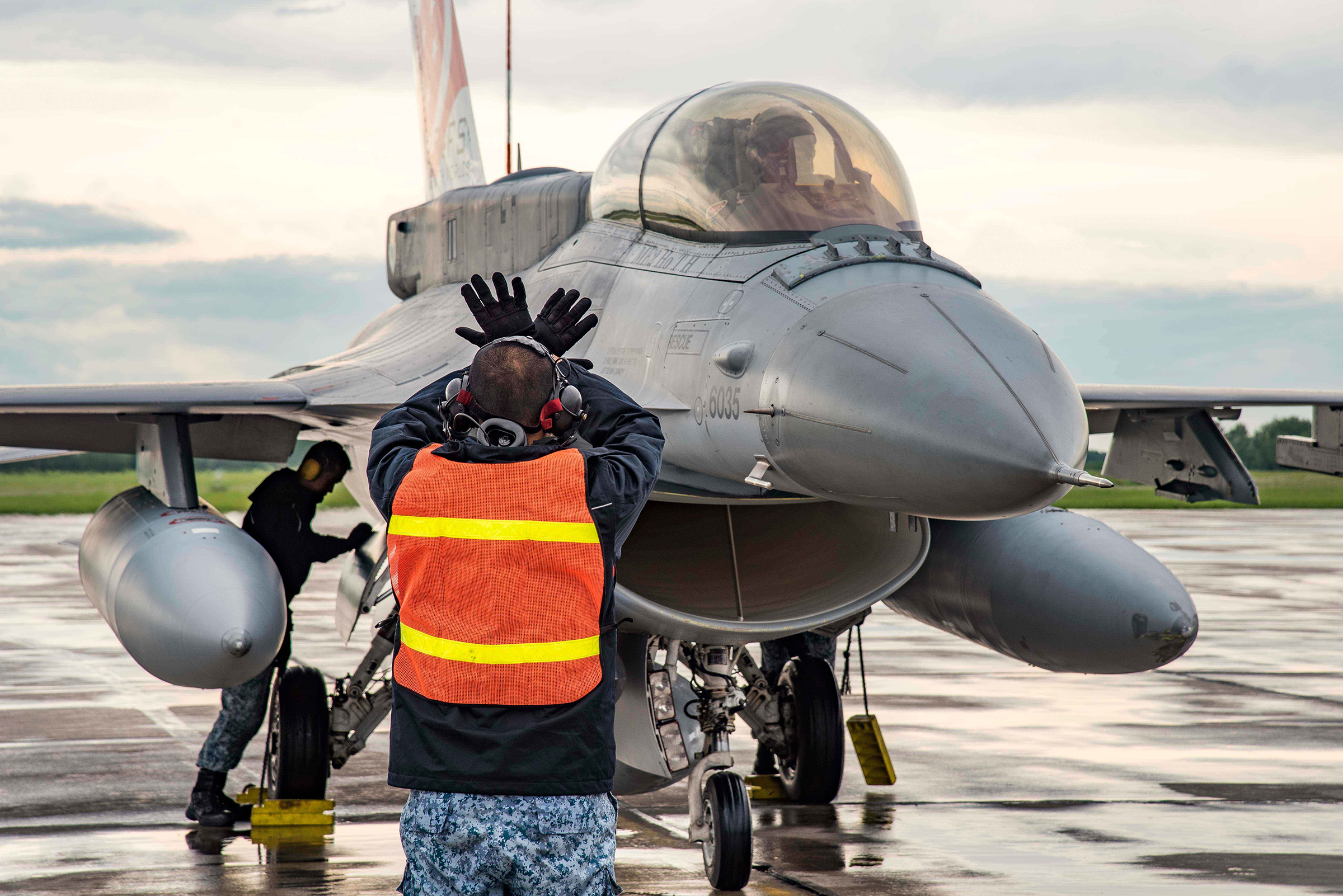 A member of the groundcrew from the Republic of Singapore Air Force, 425th Fighter Squadron, marshal one of their F-16 Falcon fighters during Exercise Maple Flag 50 at 4 Wing Cold Lake on June 9, 2017. PHOTO: Corporal Justin Roy, CK07-2017-0460-012