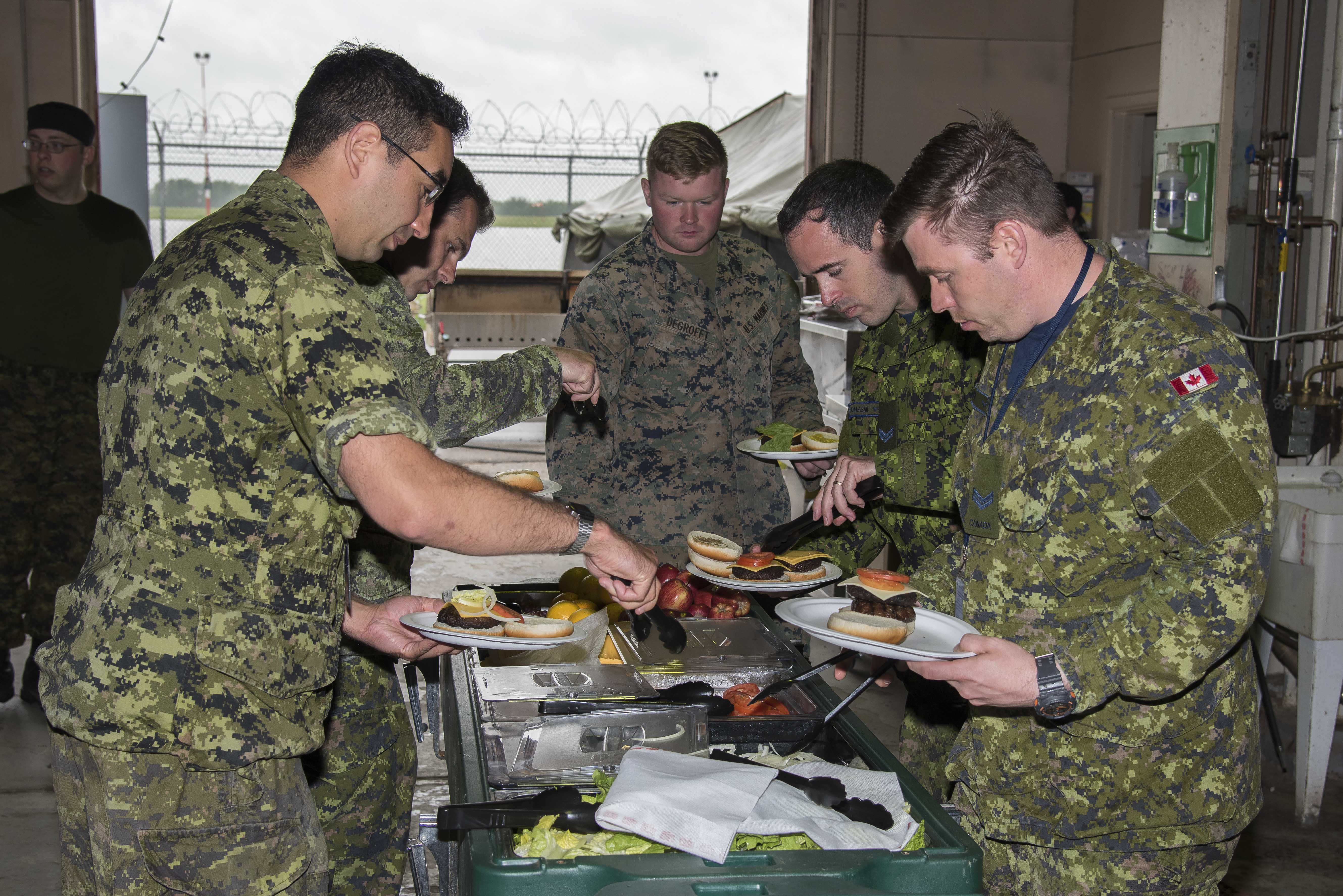 Exercise Maple Flag 50 participants assemble their hamburgers for lunch at the satellite kitchen on June 5, 2017. PHOTO: Corporal Justin Roy, CK07-2017-0464-003