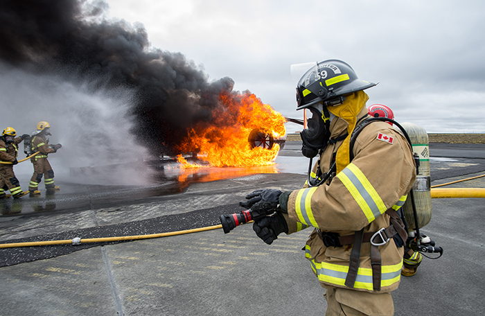 slide - On a runway, a man in the foreground wears a tan firefighting suit with reflective stripes and a black helmet, and holds an inactive firehose. In the background, two men wearing similar suits and yellow helmets use a firehose to extinguish a fire.