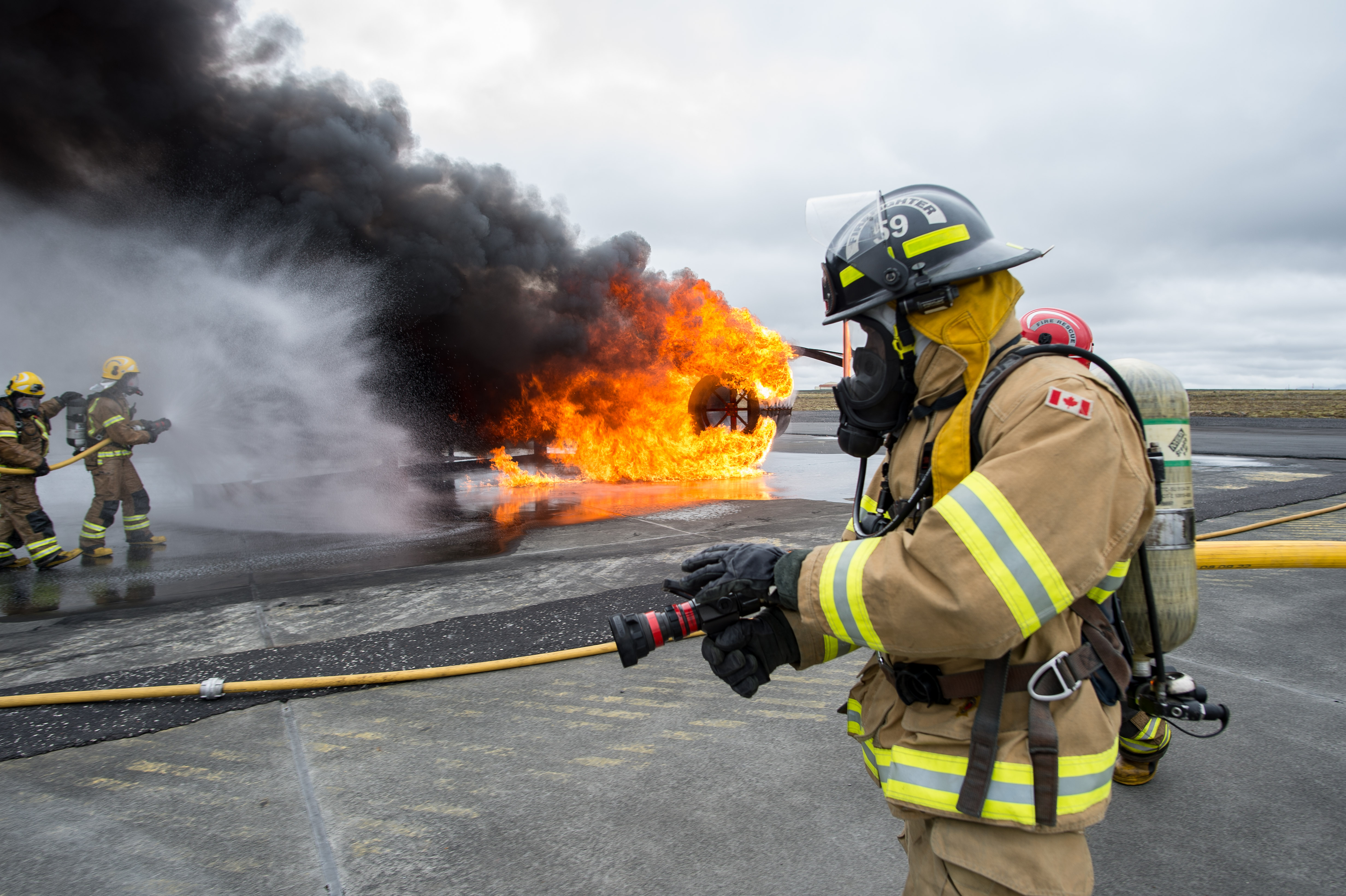 On a runway, a man in the foreground wears a tan firefighting suit with reflective stripes and a black helmet, and holds an inactive firehose. In the background, two men wearing similar suits and yellow helmets use a firehose to extinguish a fire.