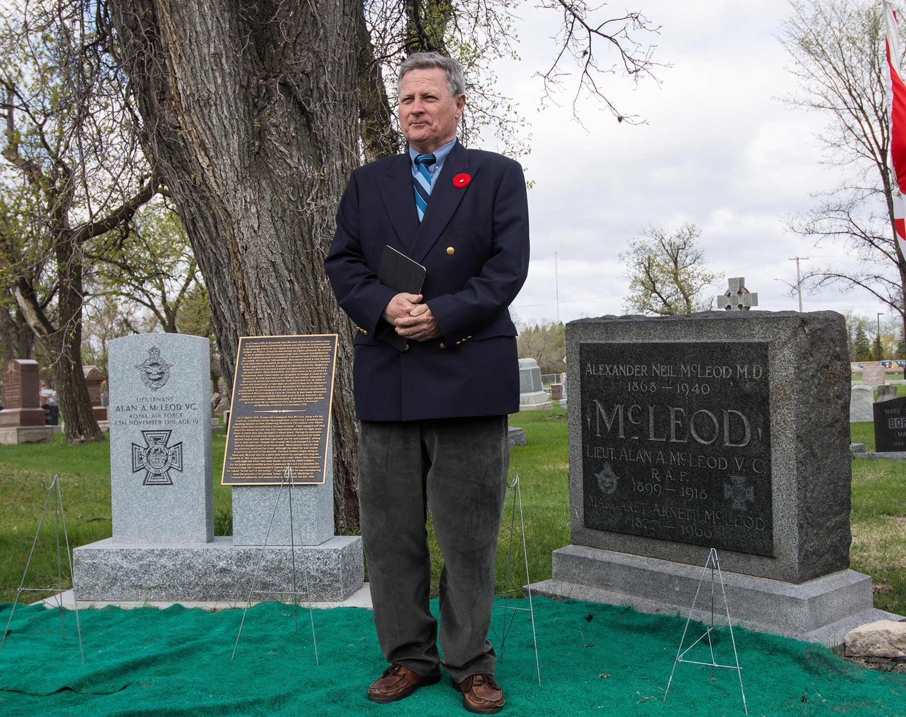 Alan Adams, the nephew of Second Lieutenant Alan McLeod, stands between McLeod's original headstone (right) and a new marker and commemorative plaque from the Commonwealth War Graves Commission that was dedicated in a May 9, 2017, ceremony at Old Kildonan Cemetery in Winnipeg, Manitoba. PHOTO: Submitted