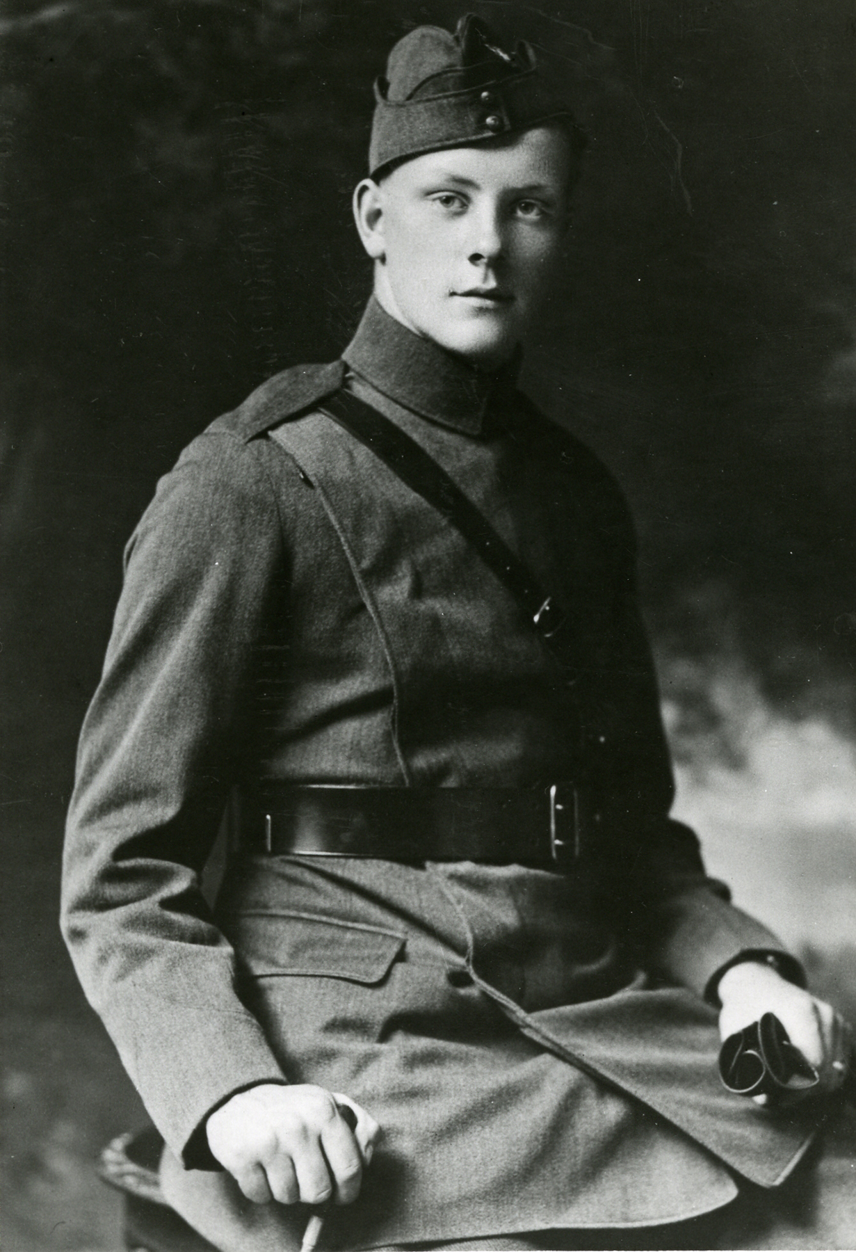 An old black and white photograph of a young man, seated, wearing a military uniform