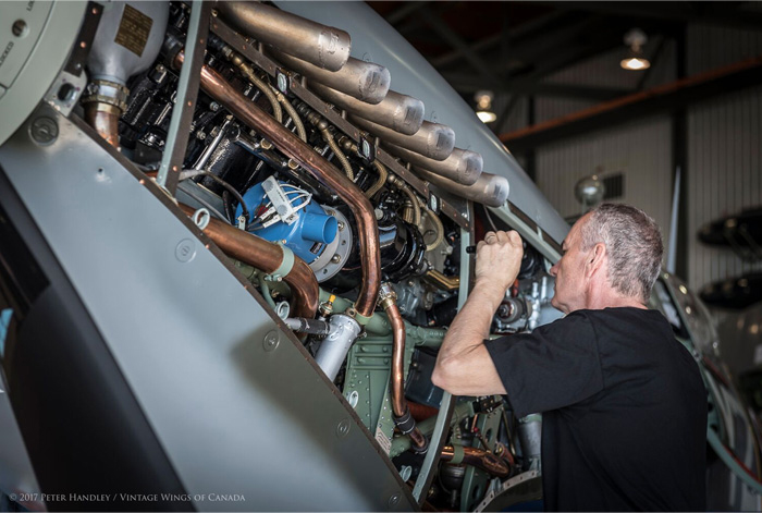After the Roseland Spitfire's first flight, mechanic Gerry Bettridge takes a closer look at its Rolls-Royce Merlin, a British liquid-cooled V-12 piston engine, checking for leaks and any signs of a problem. PHOTO: Peter Handley