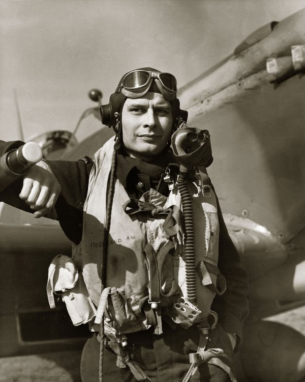 In full flying gear, Flight Lieutenant Arnold Walter Roseland stands with his Spitfire in an undated photograph.